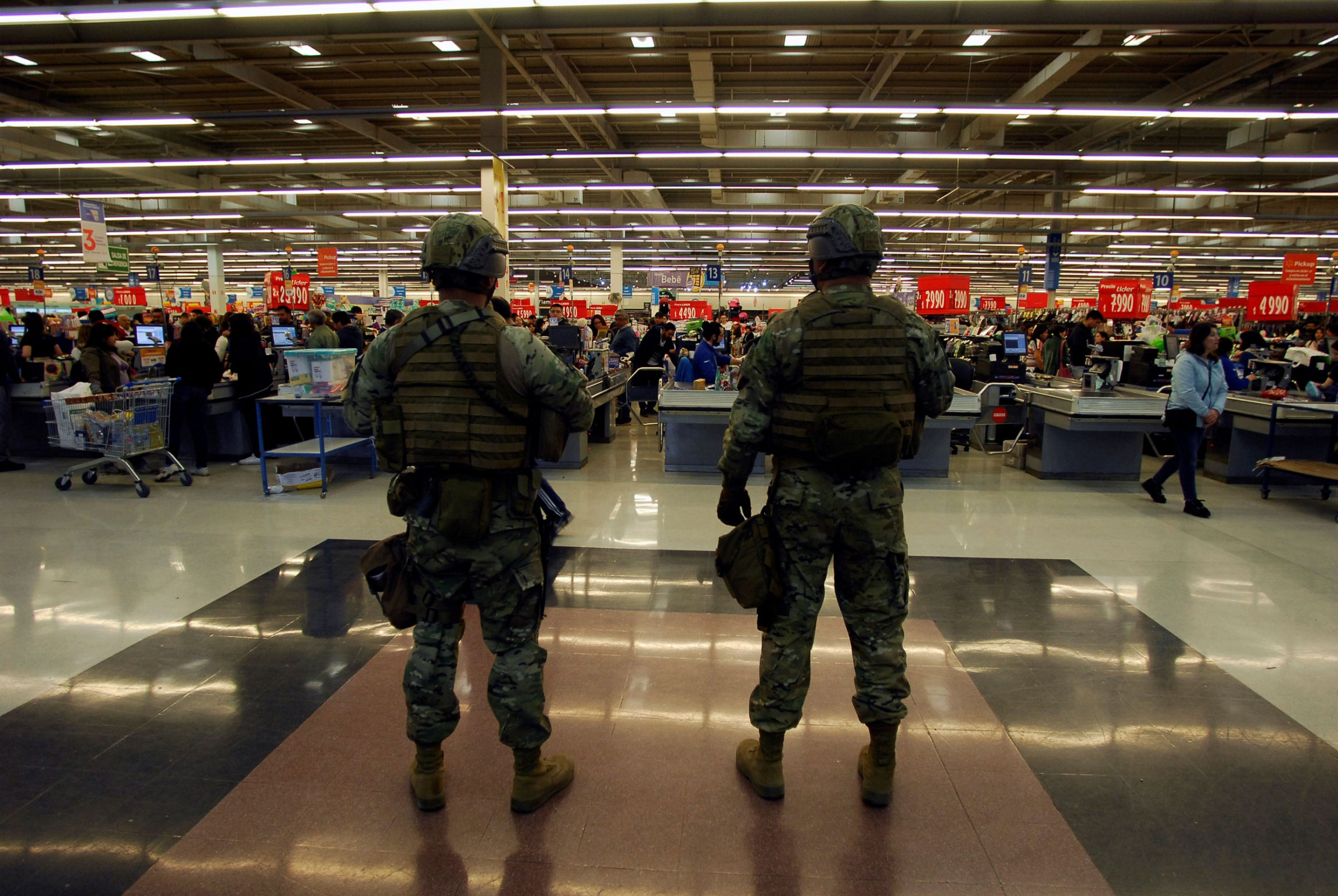 Soldiers are shown stand guard wearing full combat armor and helmets with supermarket checkout lines in the background.
