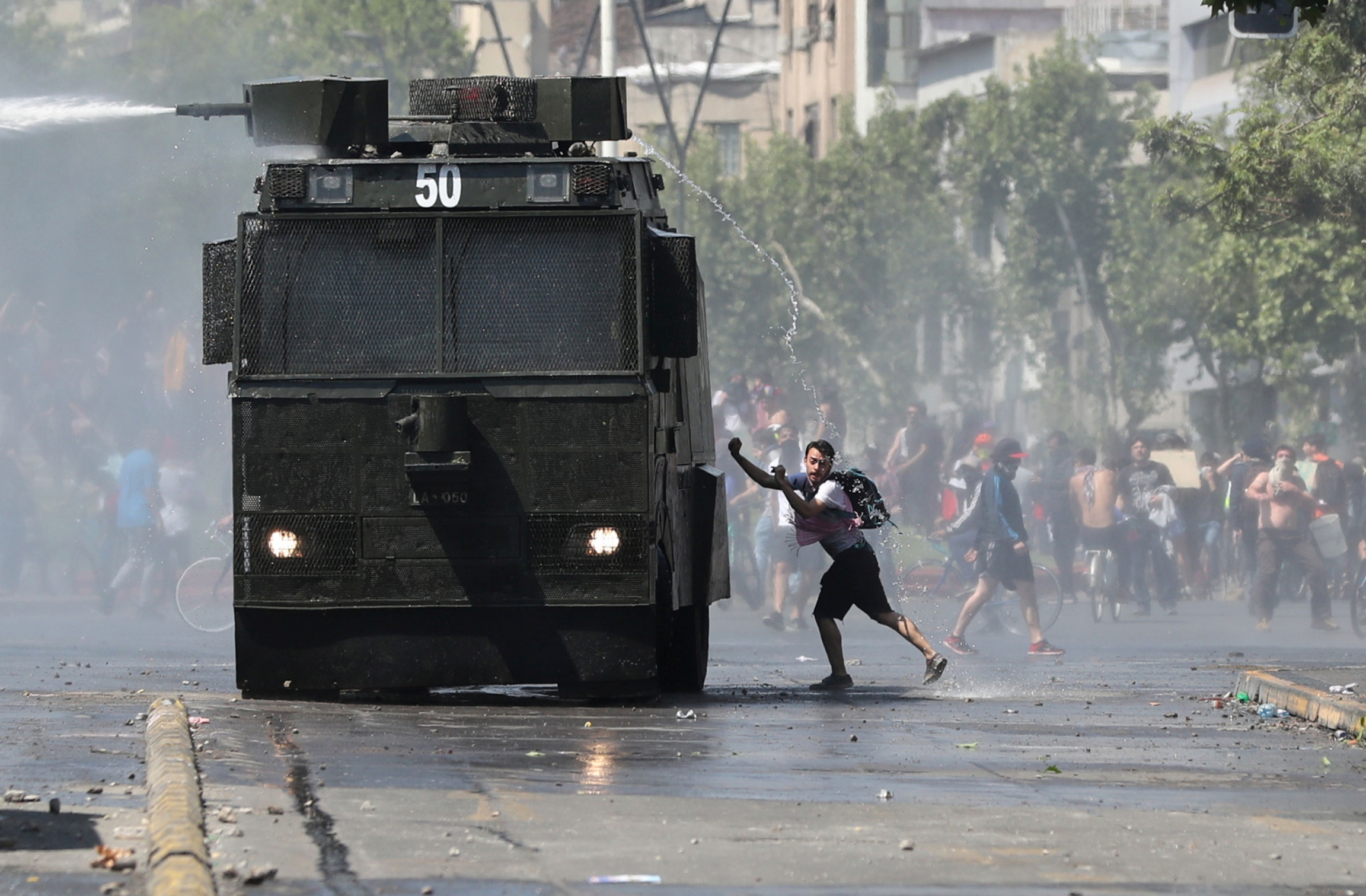 A man is shown wearing shorts and a t-shirt while getting sprayed by a police water cannon from above.