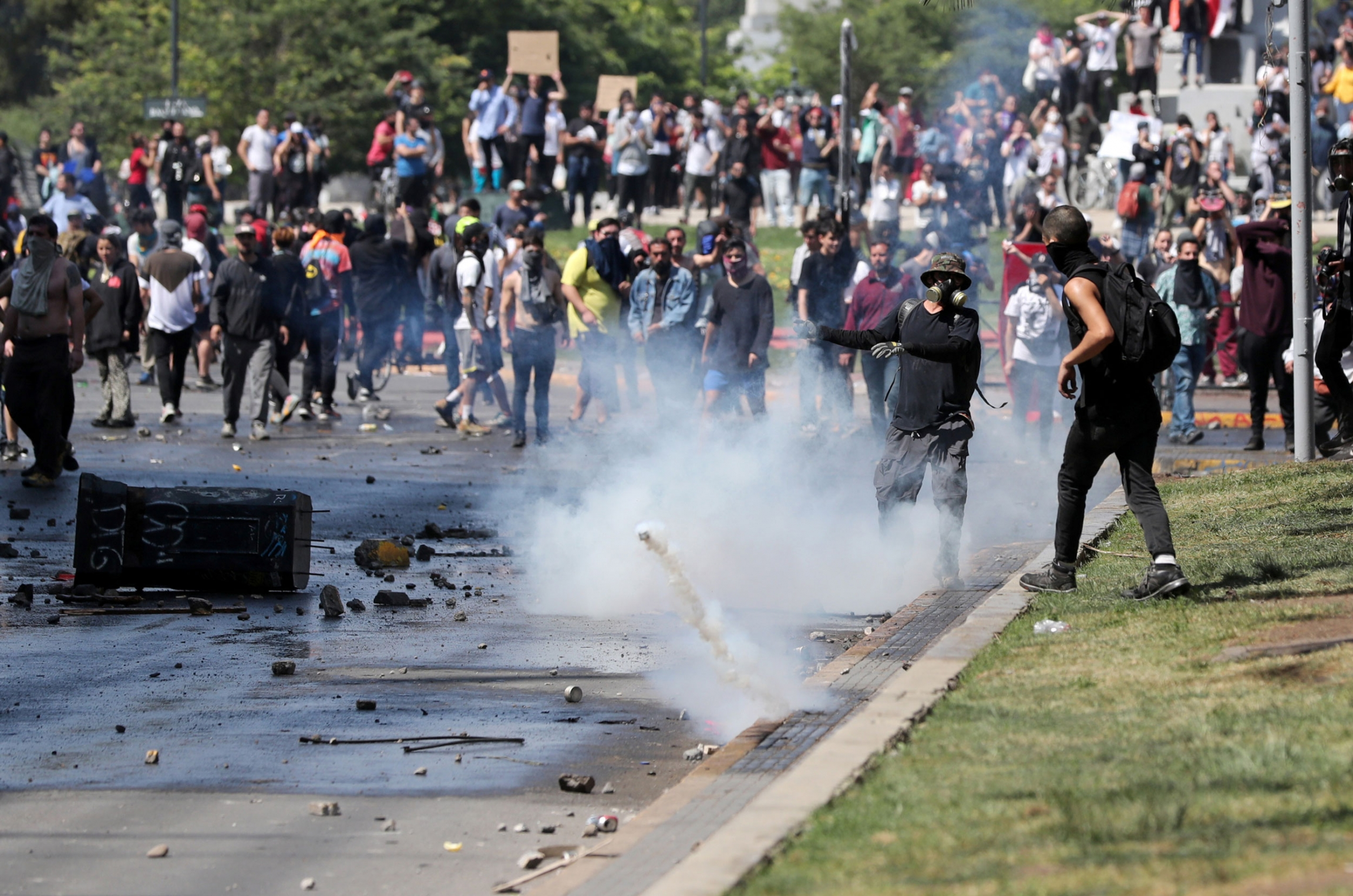 A large group of protesters are shown in the street with a smoking tear gas canister bouncing through the middle of the group.
