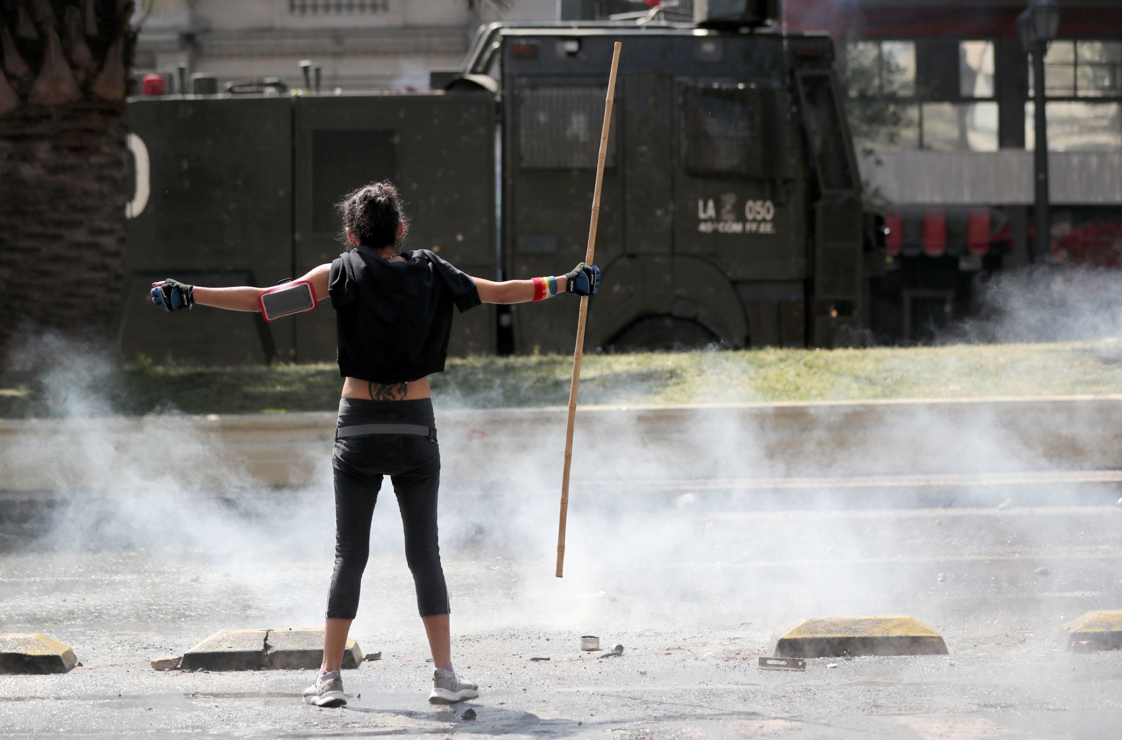 A woman is shown stands with her arms out, holding a stick, with smoke around her and a military truck in the distance.