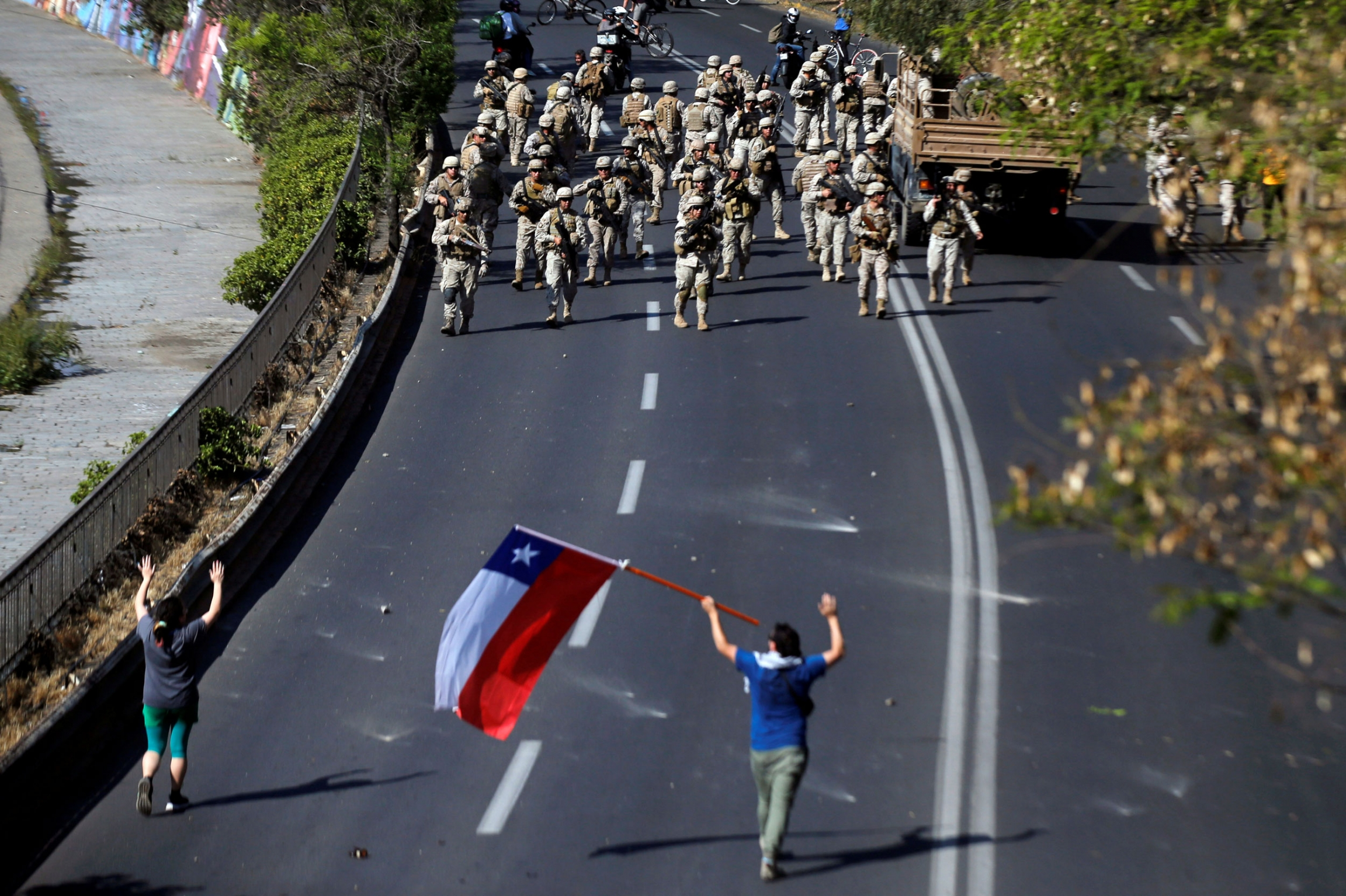 Dozens of Chilean soldiers are shown marching down a road toward two protesters, one carrying a Chilean national flag.