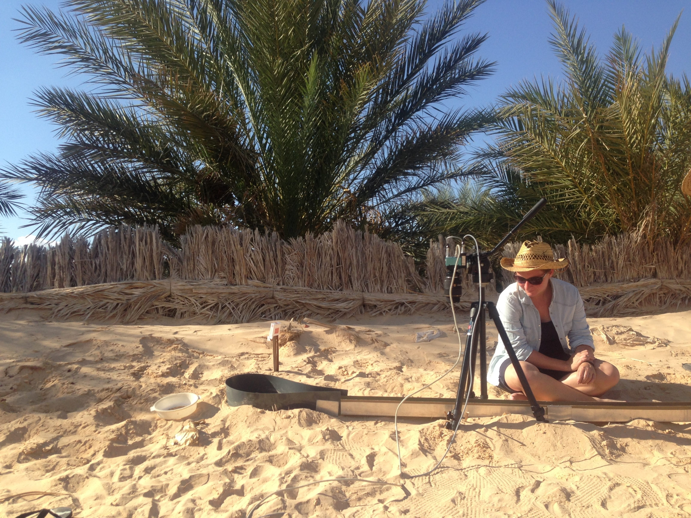 A person wearing a sun hat sets up a metal contraption in the sand.