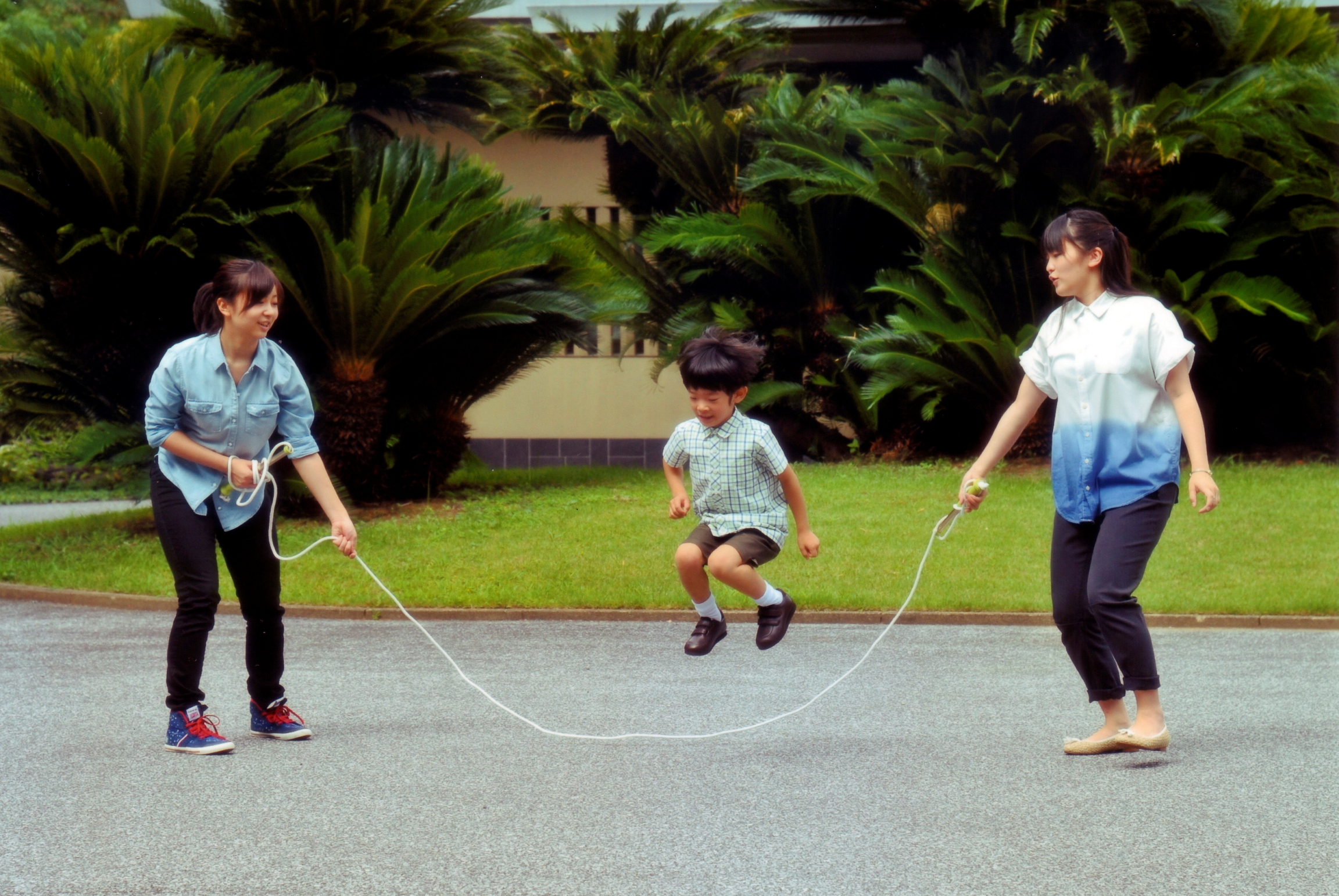 A young boy jumps rope that two young girls are swinging