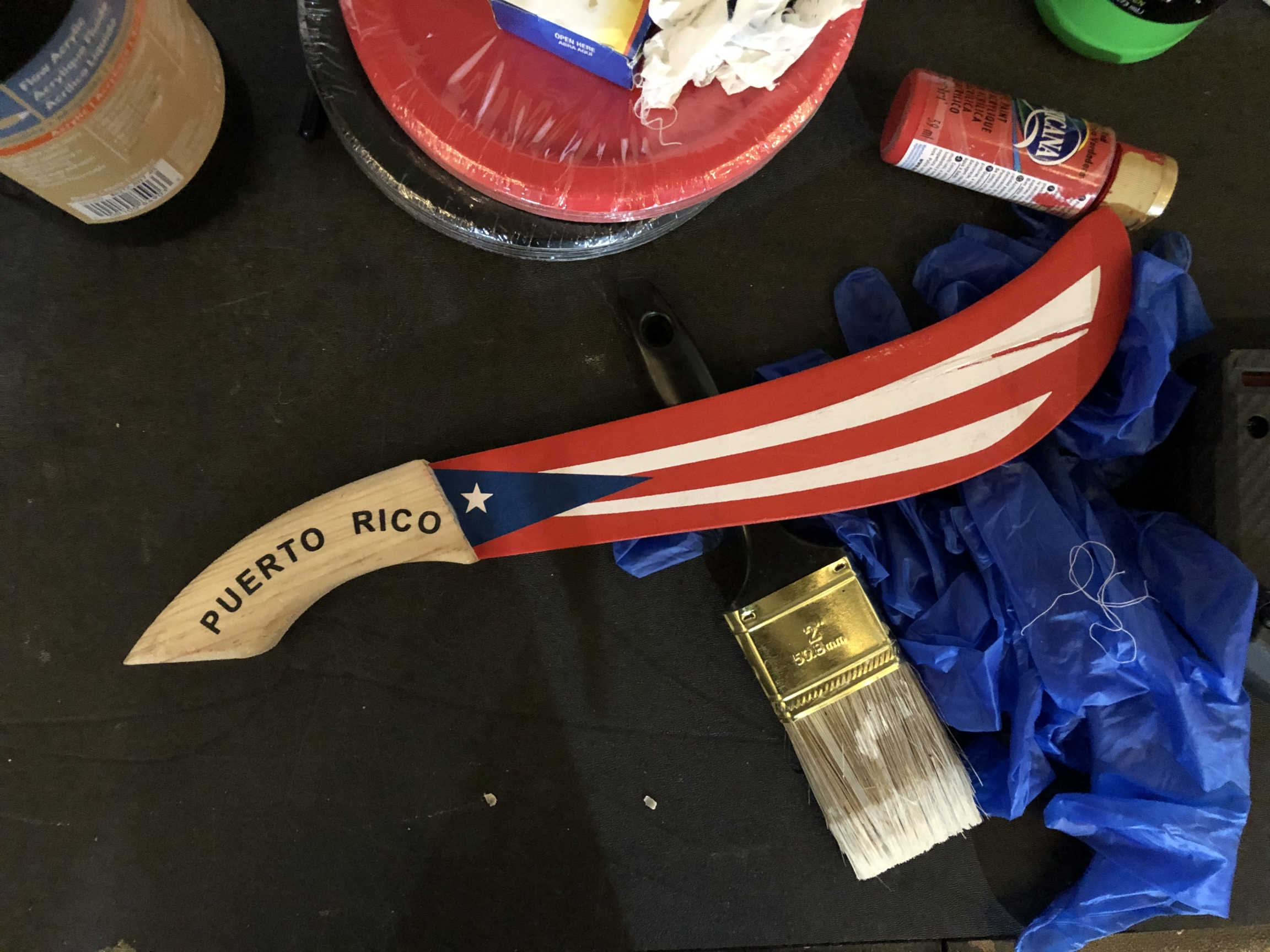 A prop wooden machete painted red, white and blue to match the Puerto Rican flag.