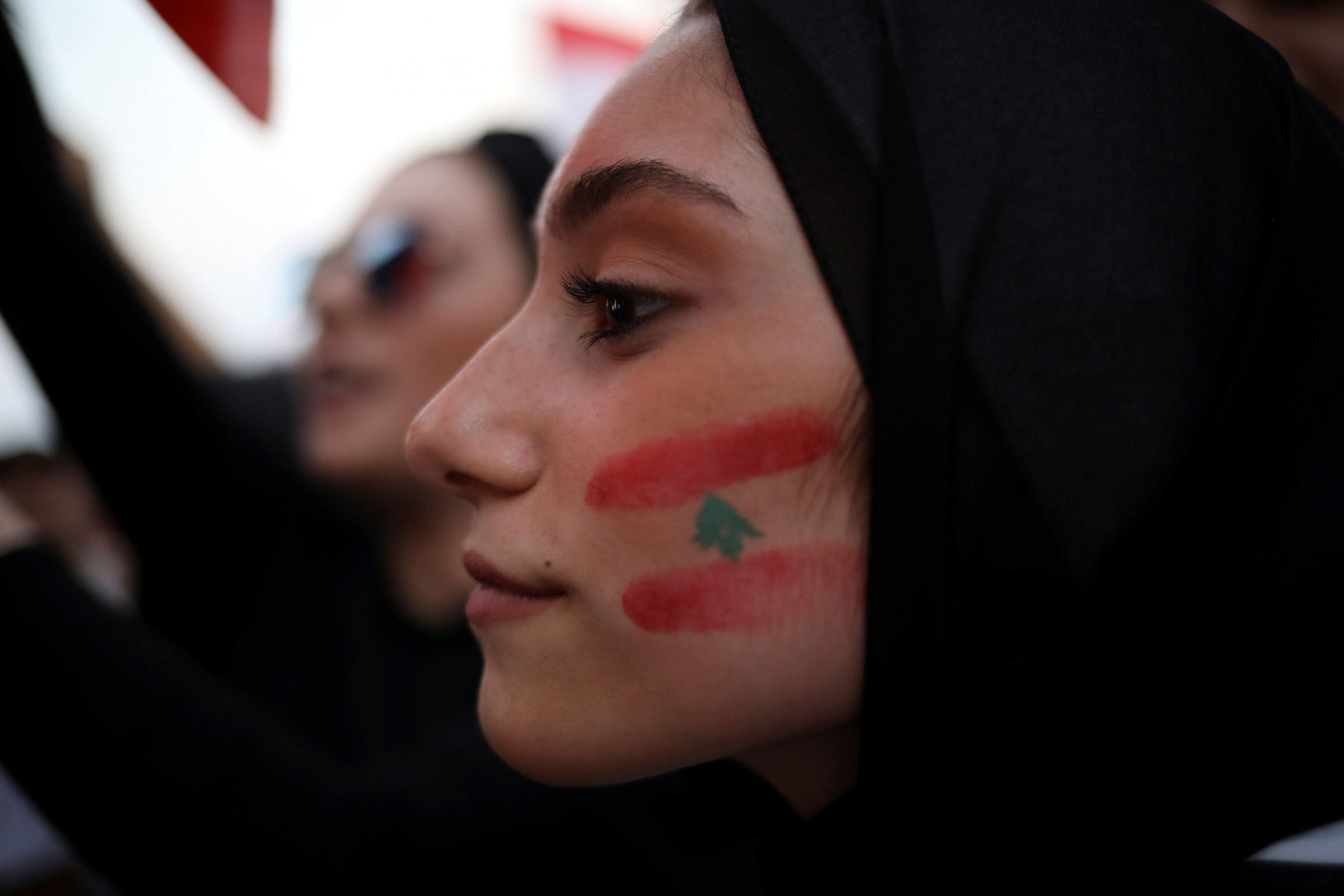 A demonstrator with a Lebanese national flag drawn on her face takes part in an anti-government protest in downtown Beirut, Lebanon, on October 22, 2019