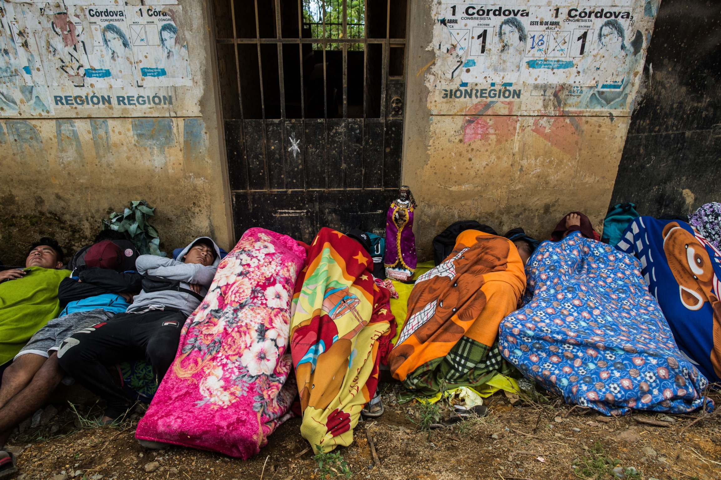 Pilgrims are shown wrapped in colorful blankets laying on the ground on the side of the road.