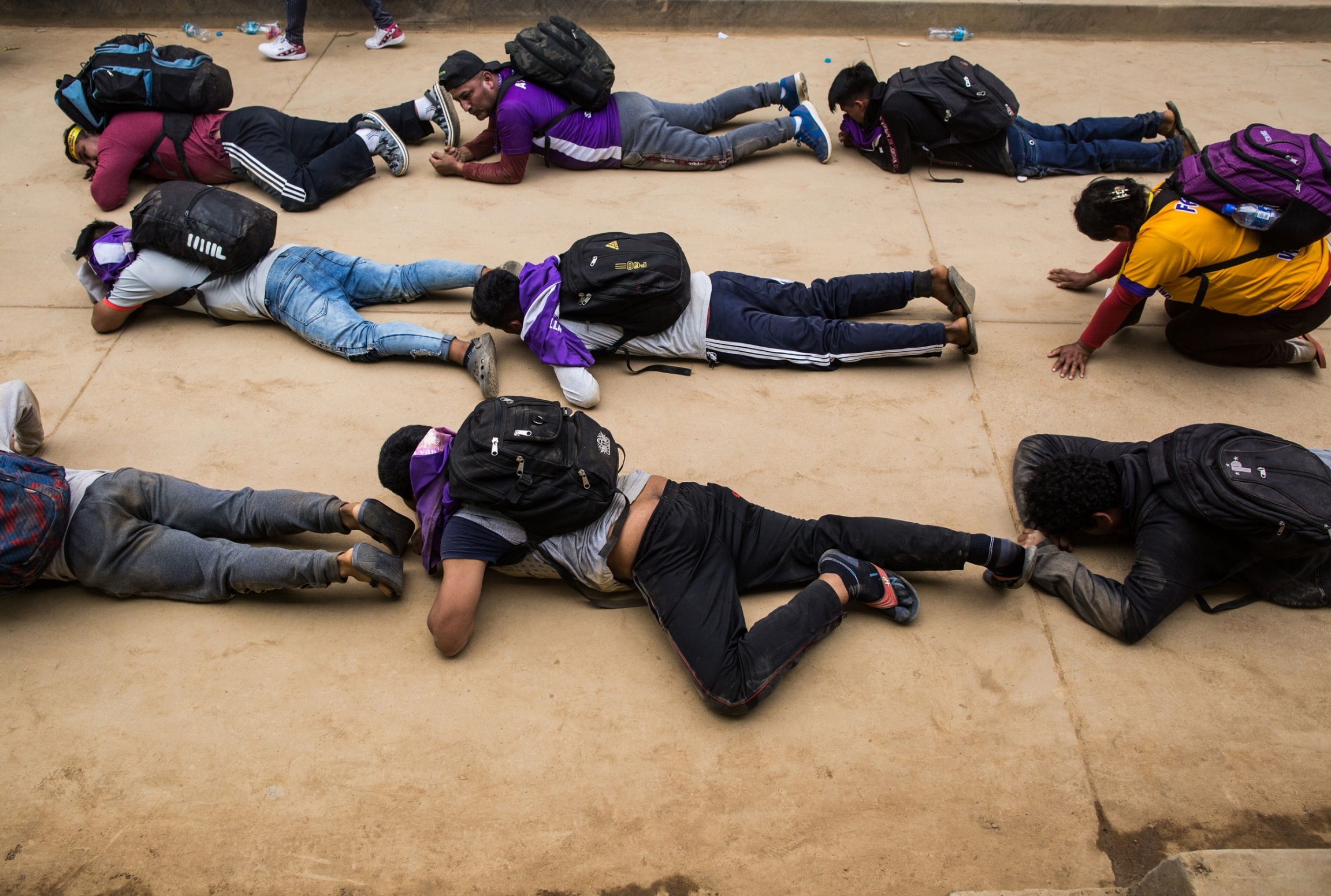 Several people are shown crawling on their stomachs on the ground and wearing backpacks.