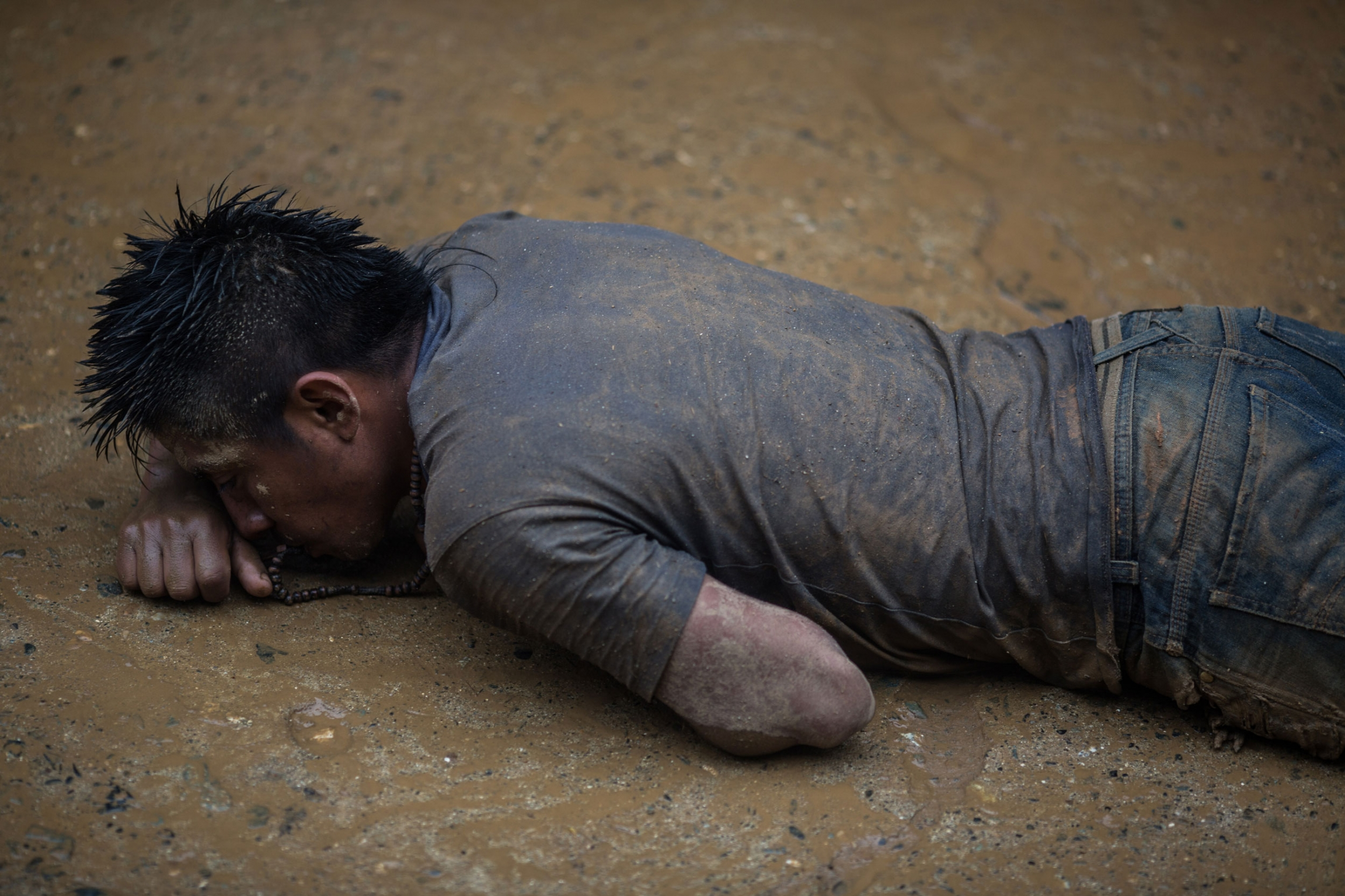 A man is shown crawling on his stomach in the mud and covered in dirt.