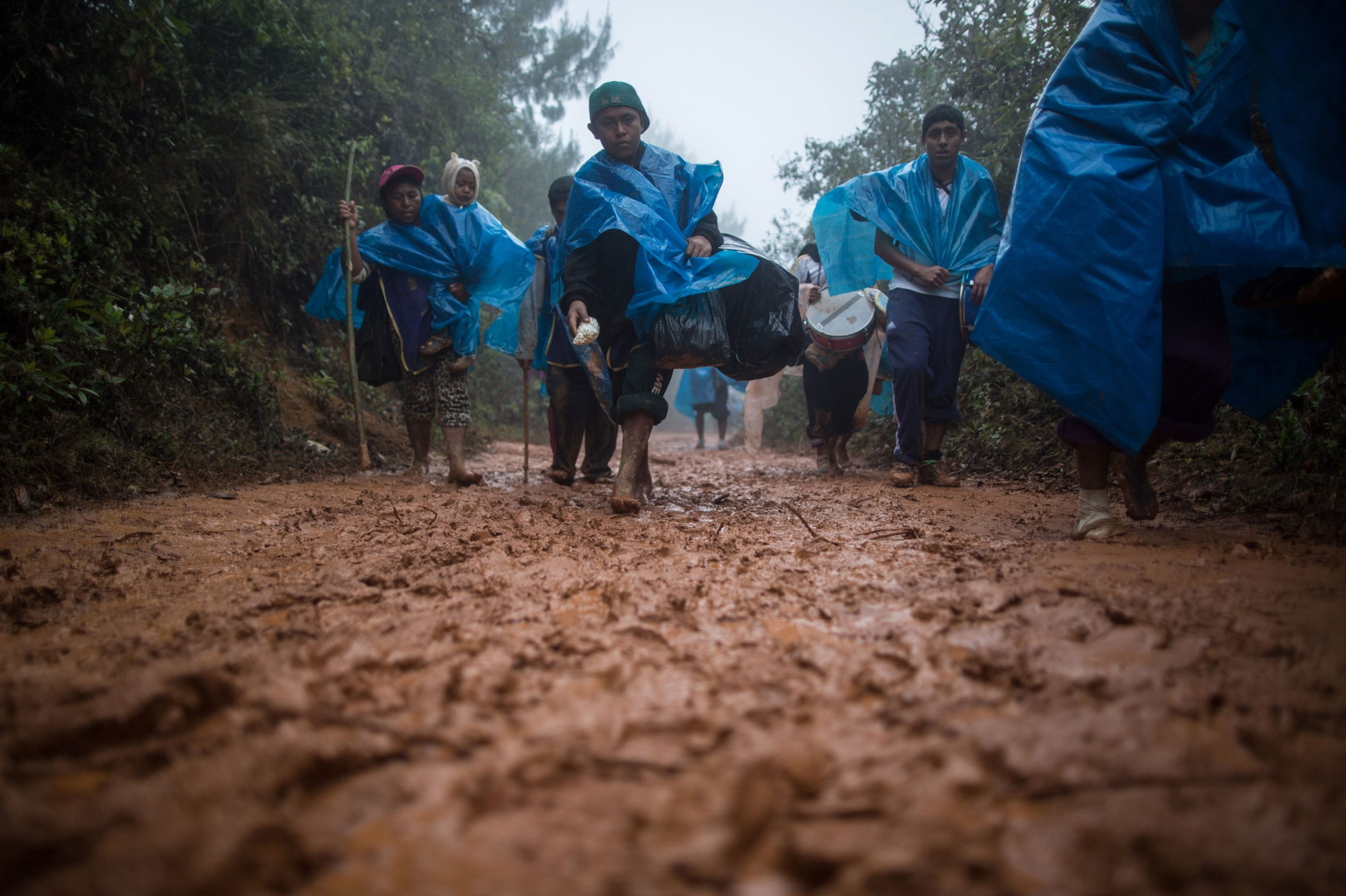 Several people are shown walking along a muddy path and wearing blue rain ponchos.