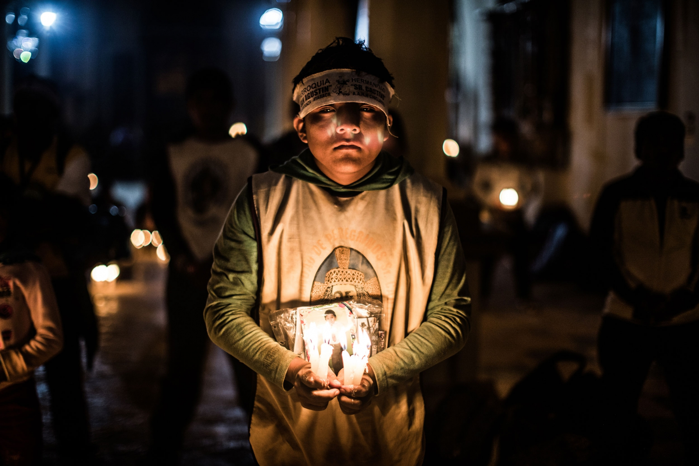A you boy is shown holding several candles and a picture in a darkly lit photograph.