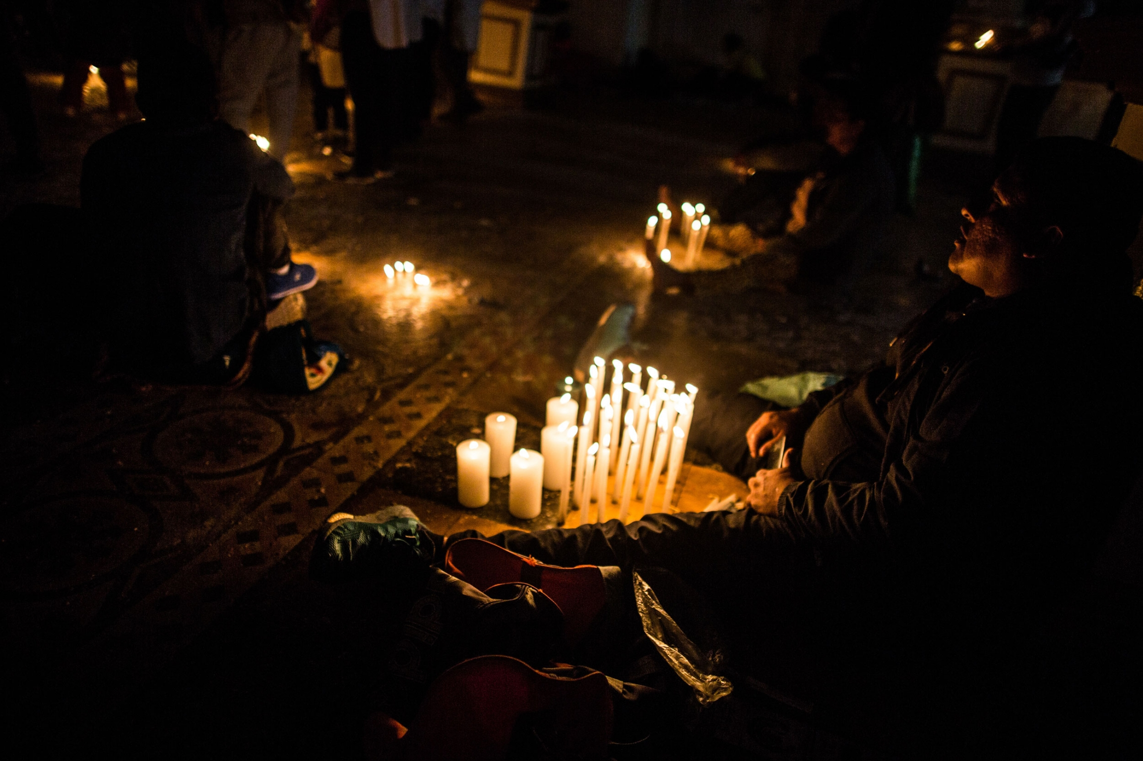 A person is shown sitting on the ground with their legs on either side of a display of several lit candles.