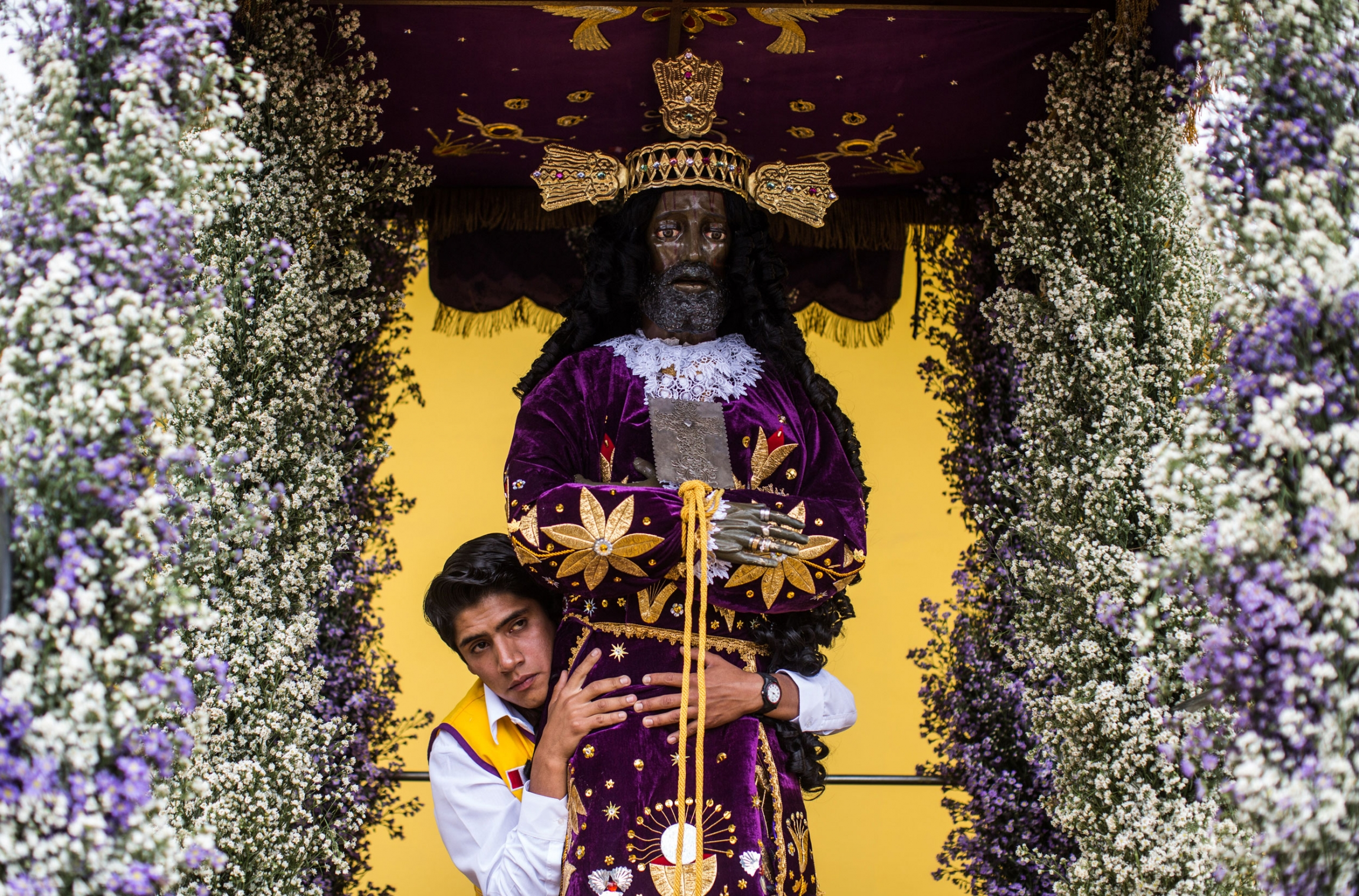A young man is shown standing behind a carved statue of the Captive which is adorned with a decorative religious robe.