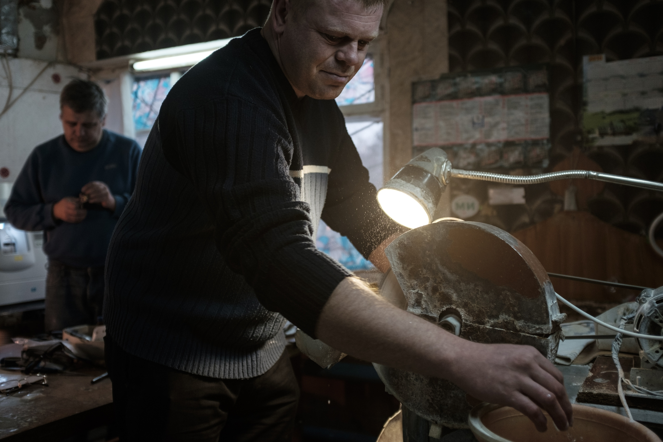 A man in shadow works at a grinder