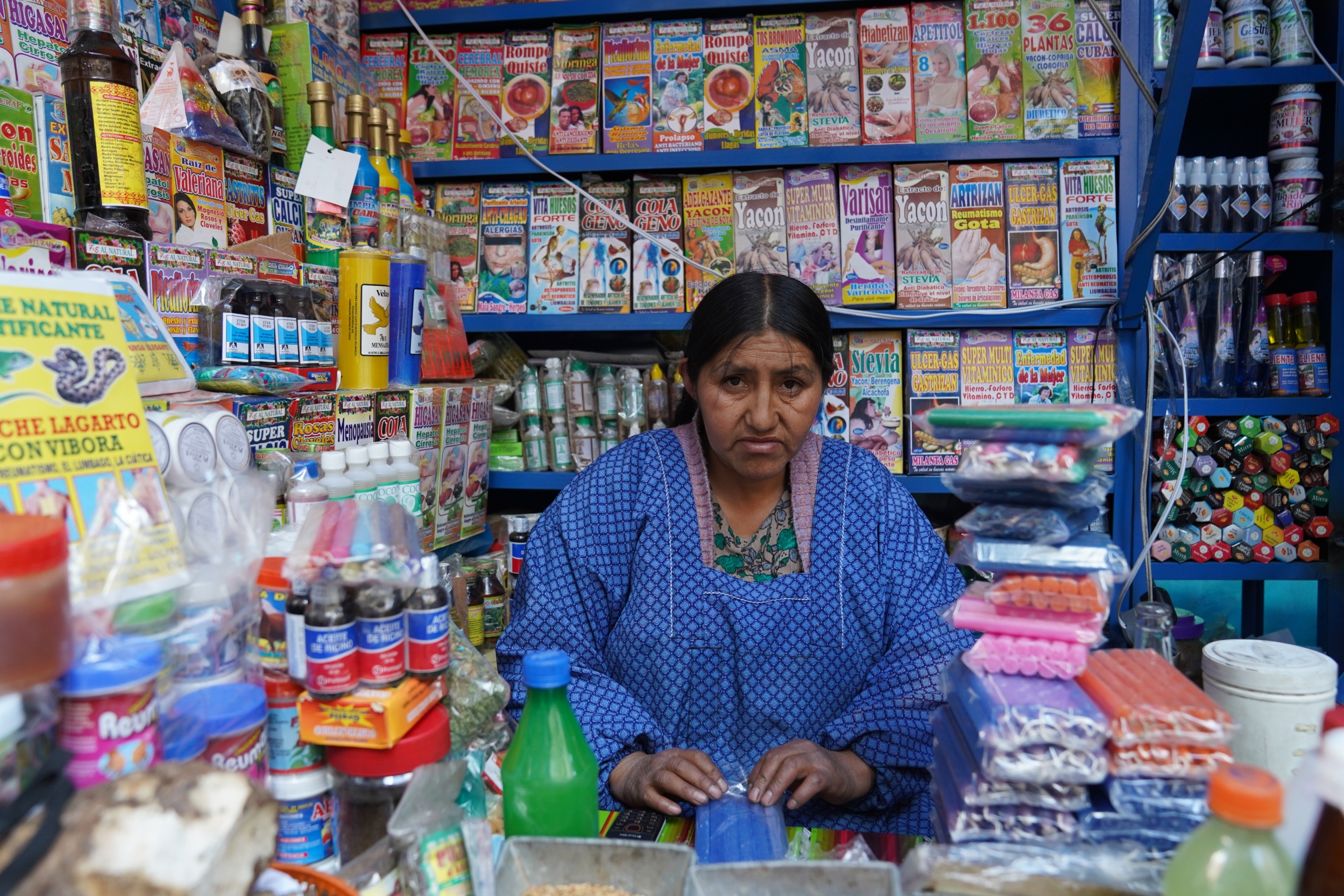 Morales supporter wearing a blue top stands in a fully-stocked shop with bright and colorful products stacked behind her.