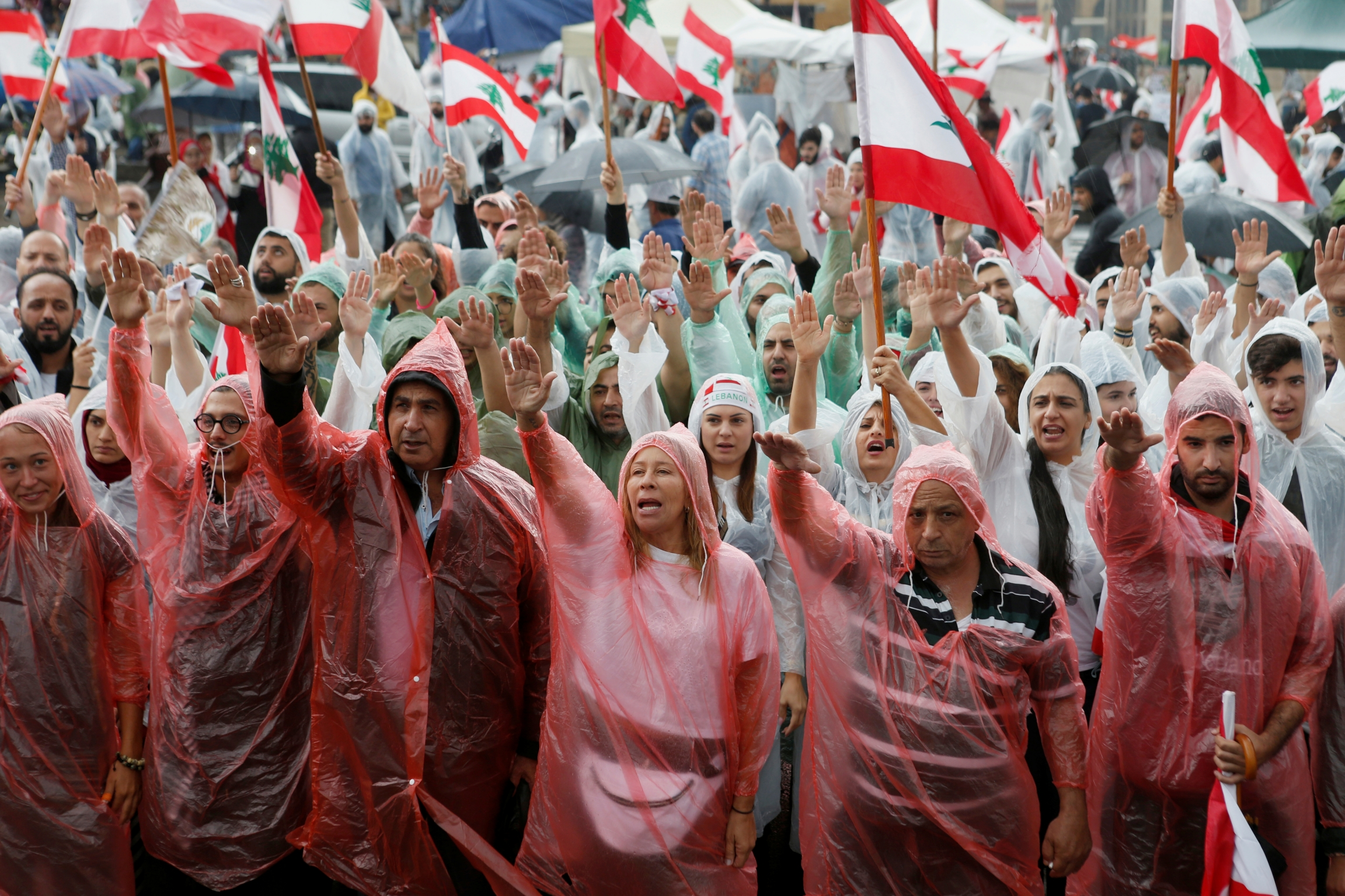Demonstrators, covered in rain coats, gesture and carry flags during ongoing anti-government protests in downtown Beirut, Lebanon, Oct. 24, 2019.