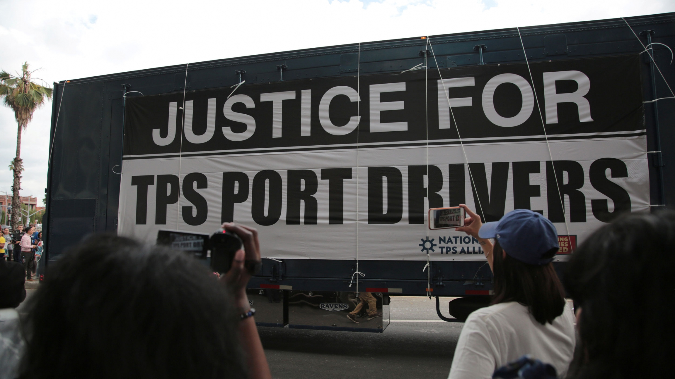 "A large sign hanging off the side of a tractor reads ""Justice for TPS Port Drivers"""