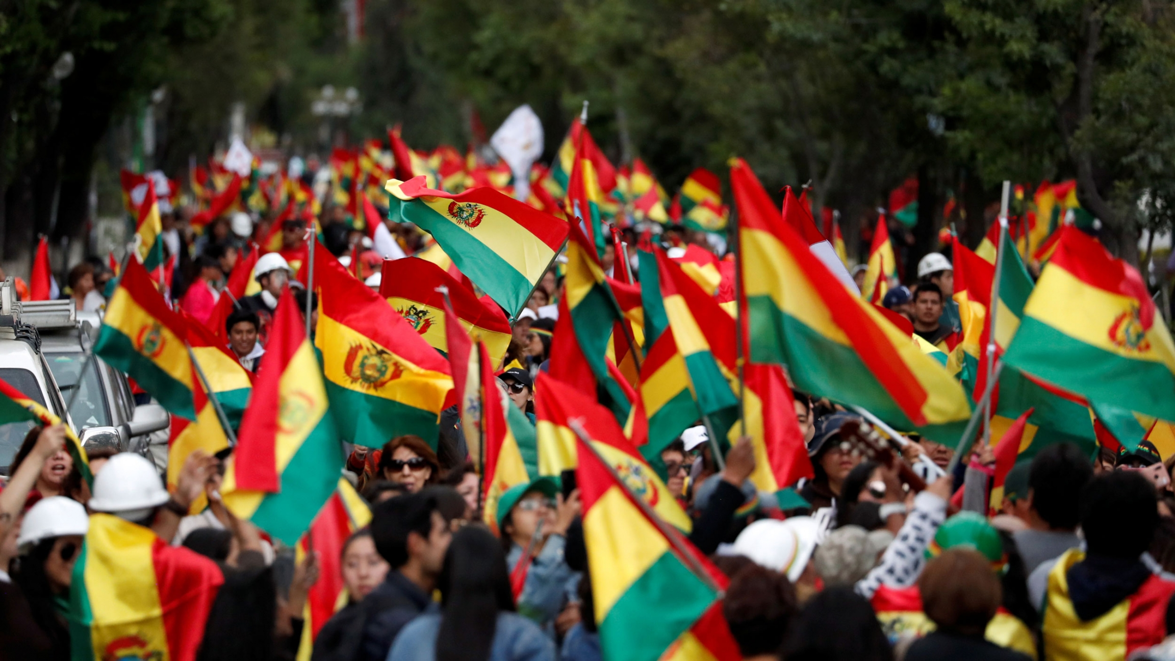 Protesters hold Bolivian flags above their heads as they pack a street