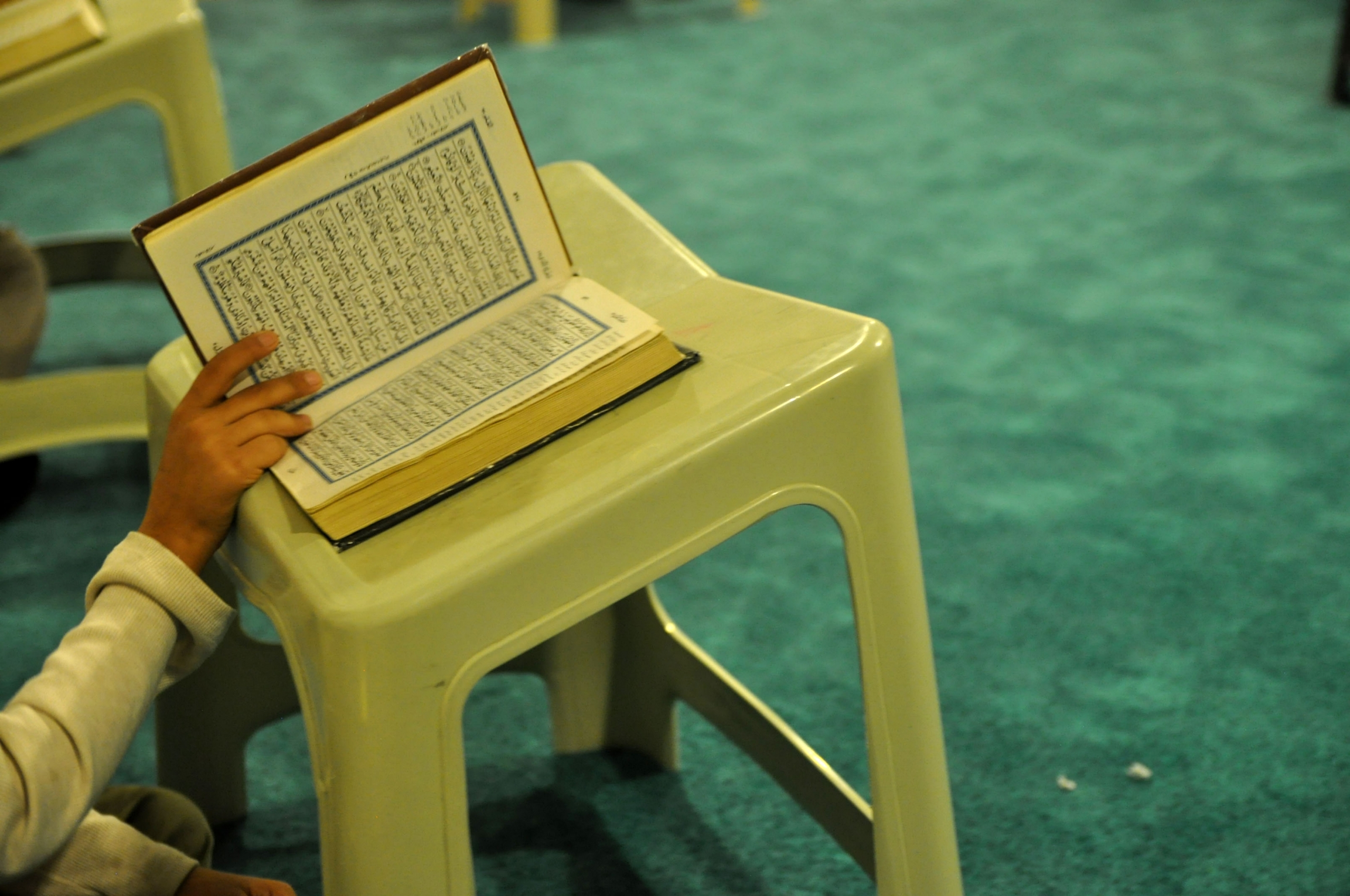 A hand holds the Quran open on a stool near green carpet