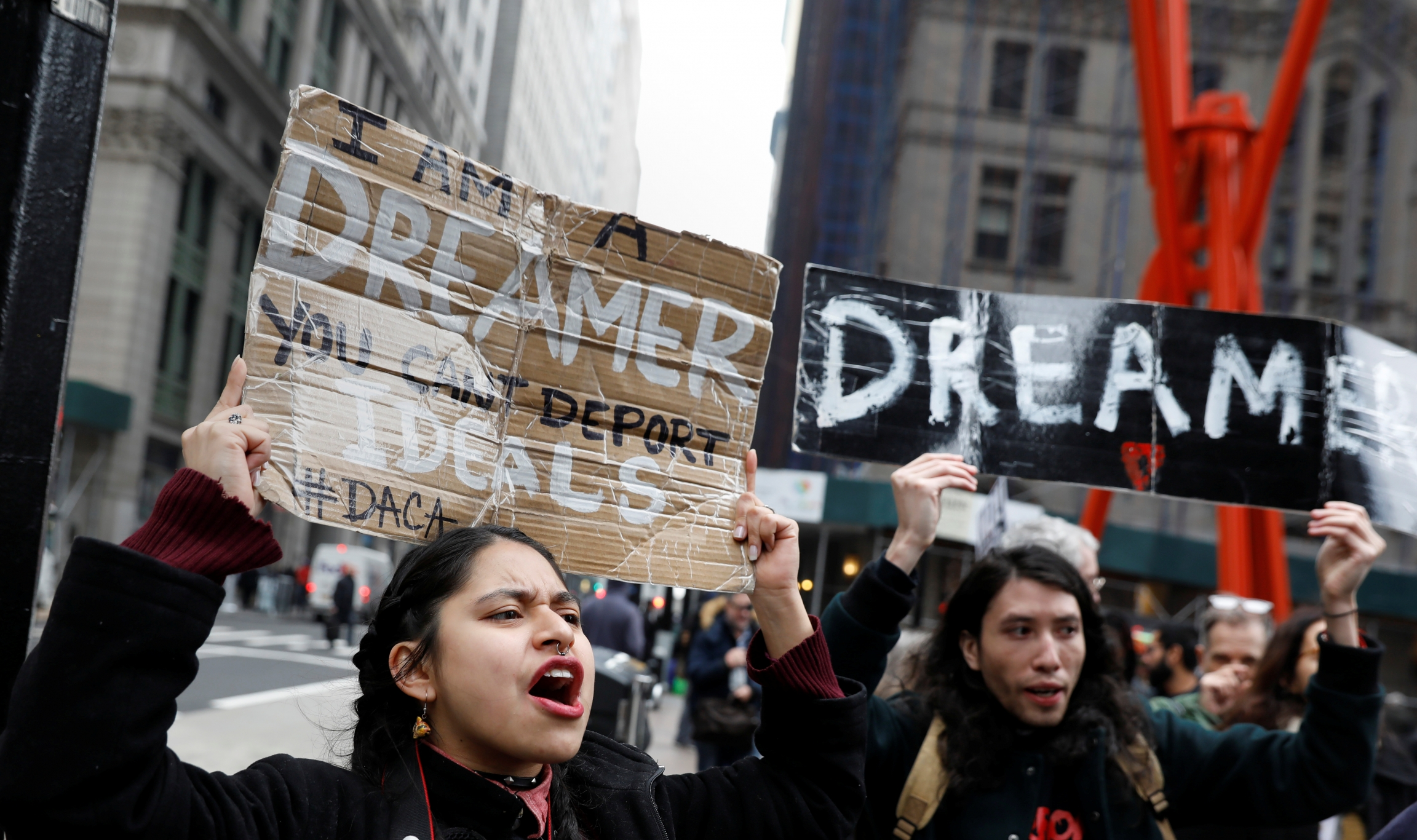 Activists and DACA recipients march up Broadway in New York holding signs.