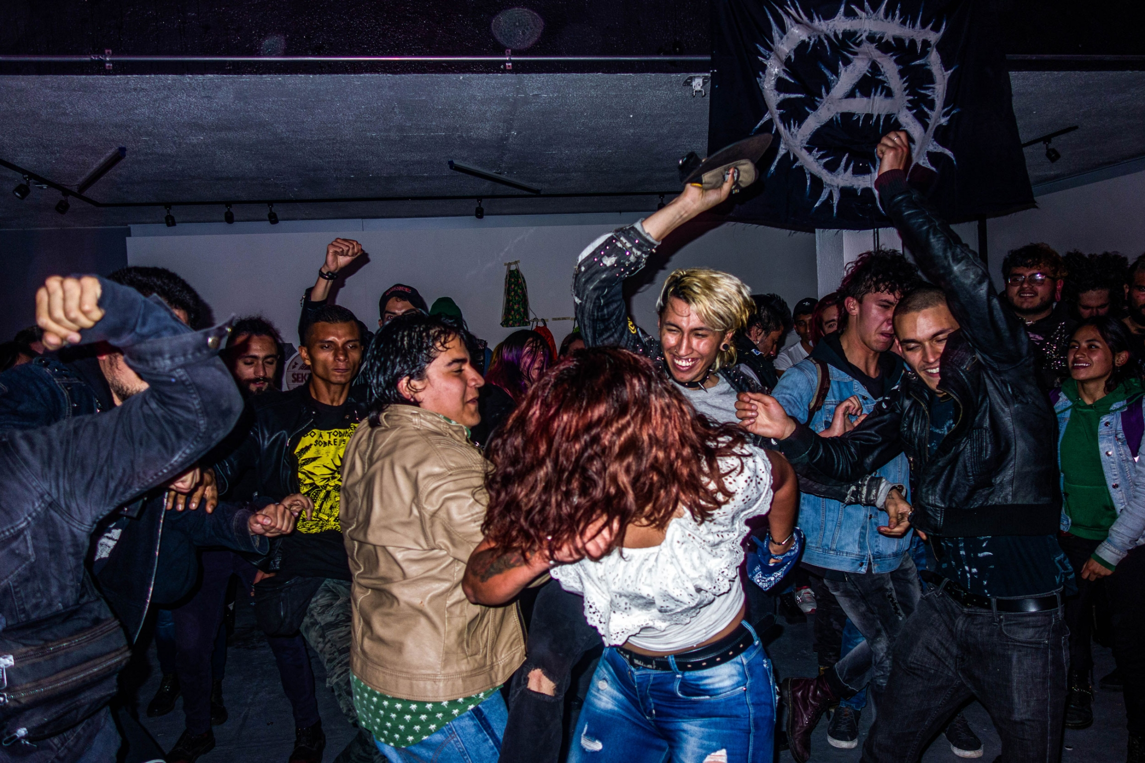 Concert-goers are shown throwing their bodies around at each other at a punk concert.