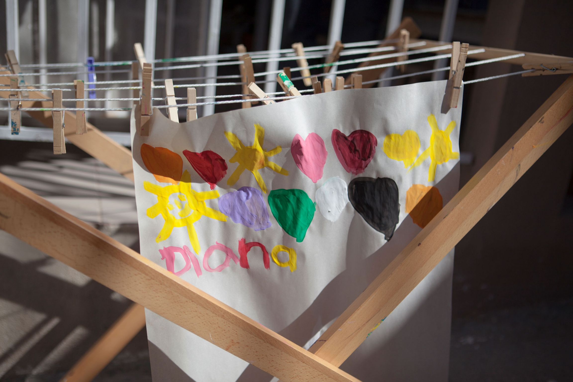 A white paper is shown with colorful hearts painted on it hanging from a wooden rack.