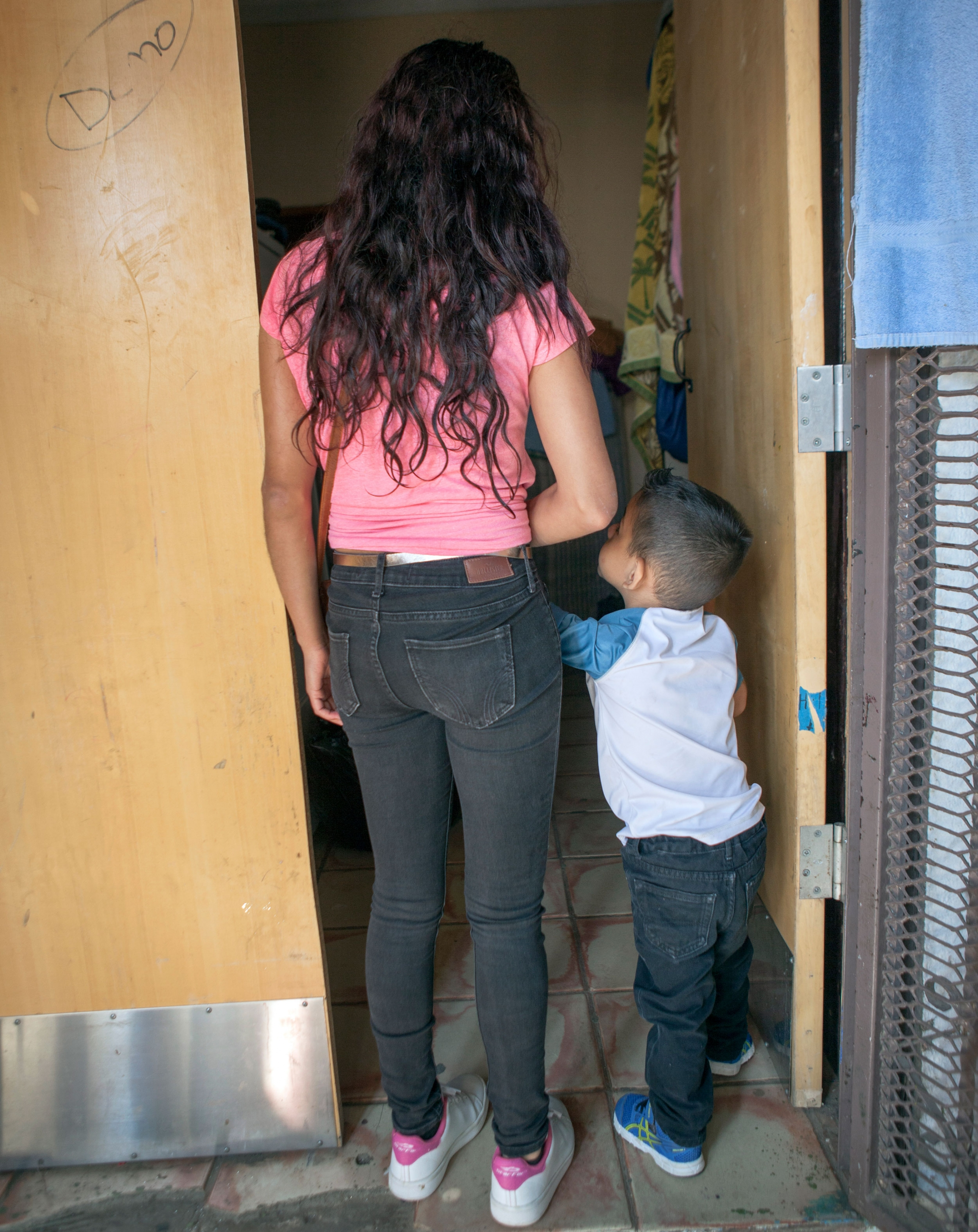 A woman is shown from behind and wearing a pink shirt and holding the hand of her son who is wearing a white shirt.