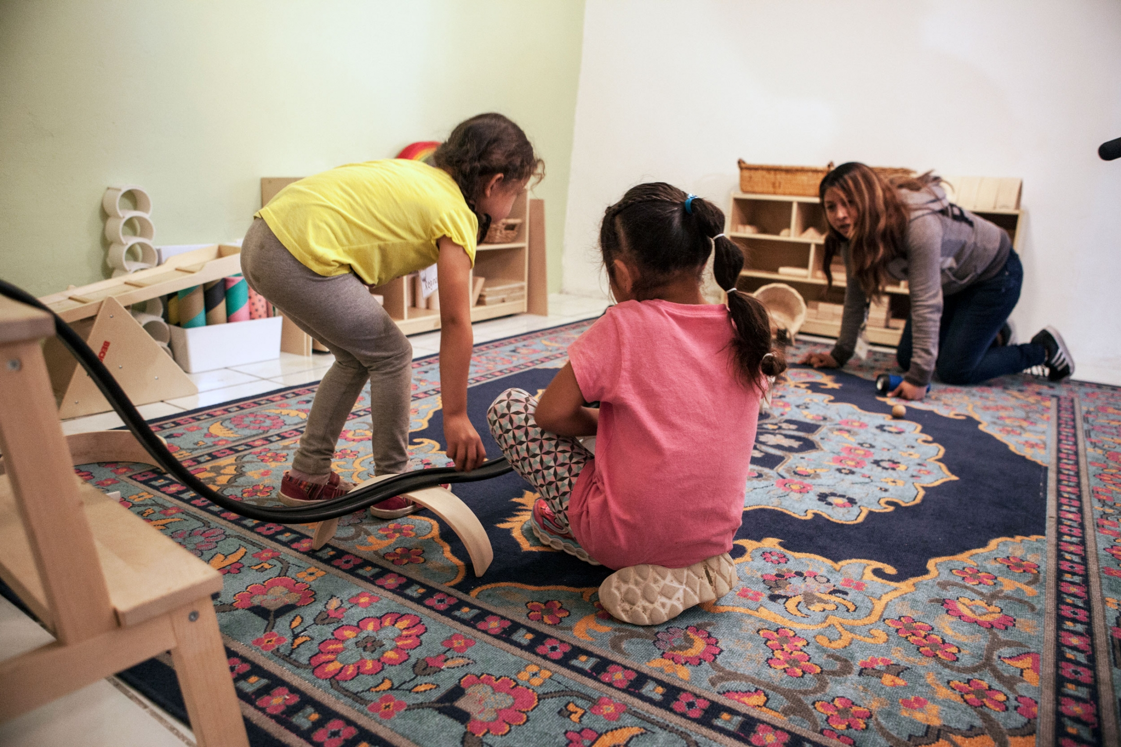 Two young girls are shown playing with a toy racing track.