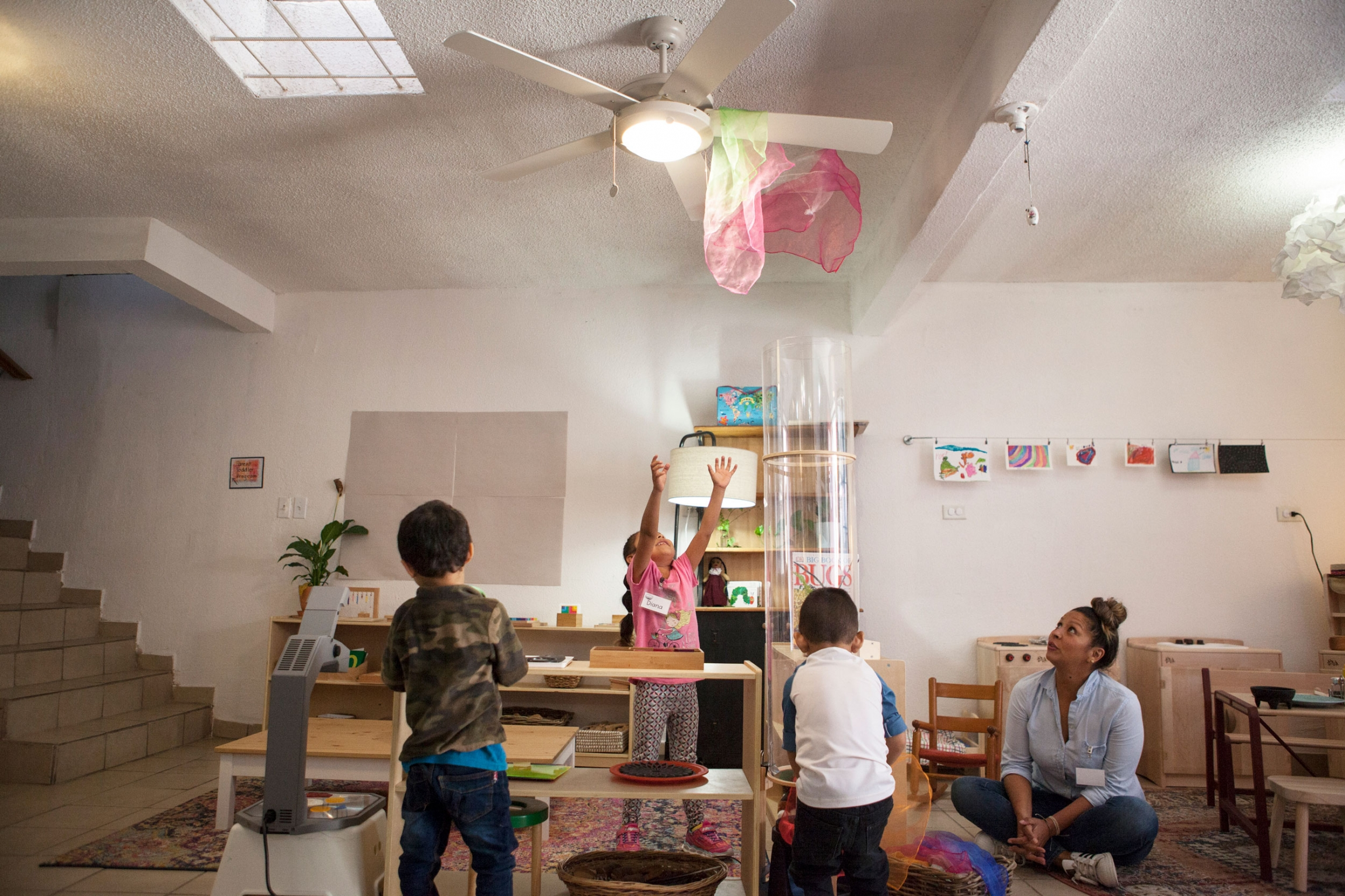 Several children are shown playing with a pink and white scarf shown caught attached to a ceiling fan.