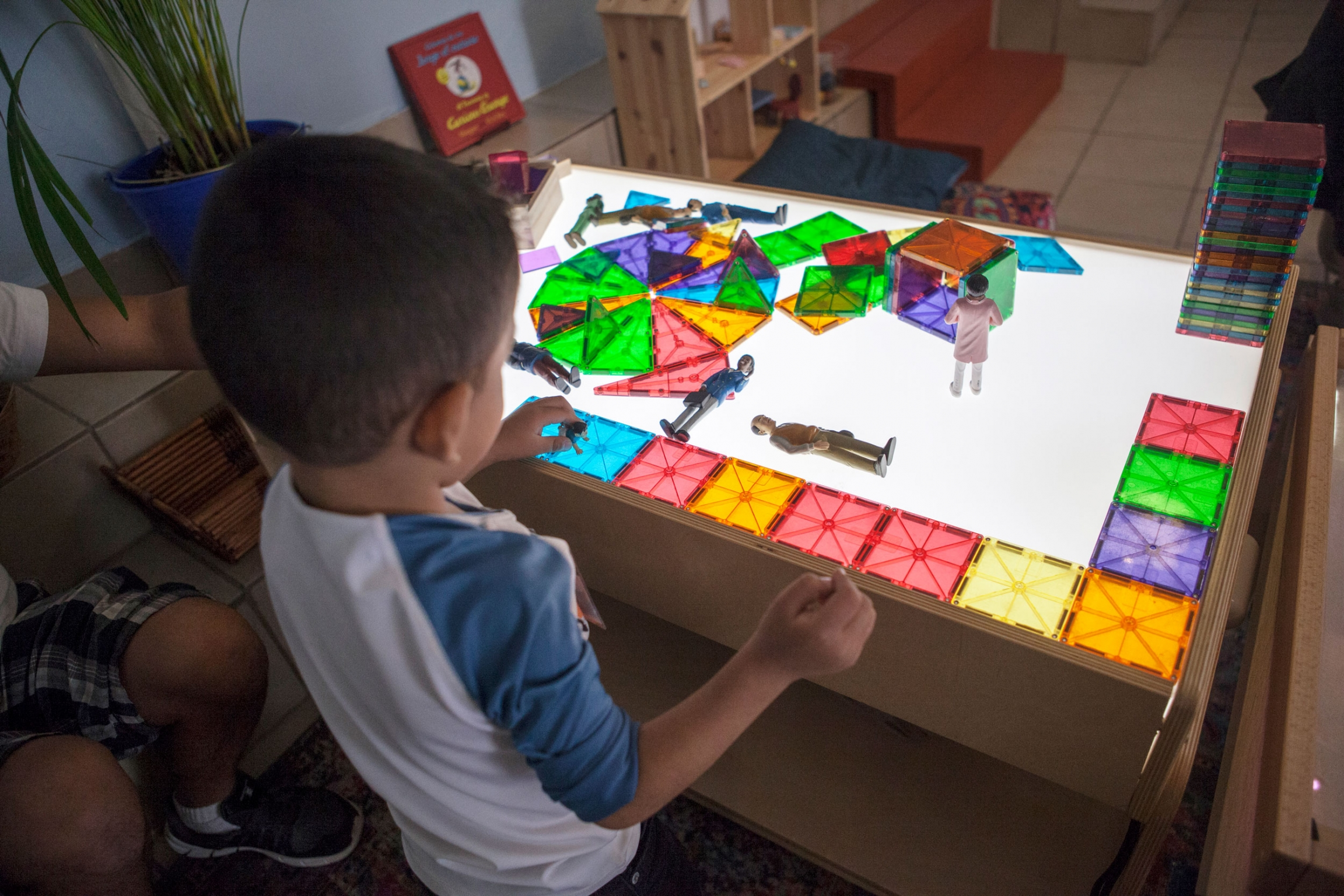 Three-year-old Kevin is shown playing at a table with color-squares illuminated by a table light.