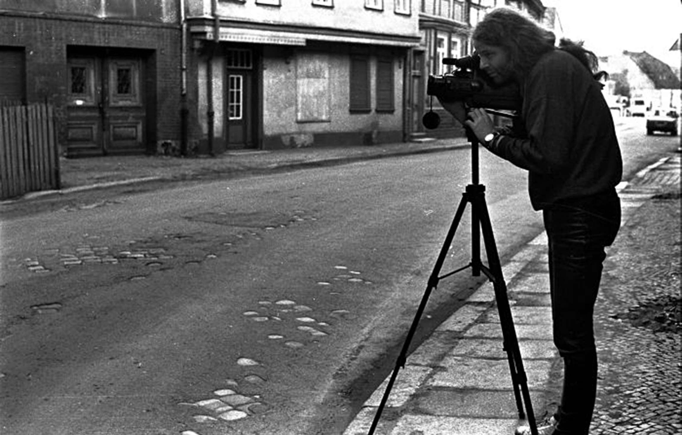 Siegbart Schefke is shown standing behind a camera on a tripod.