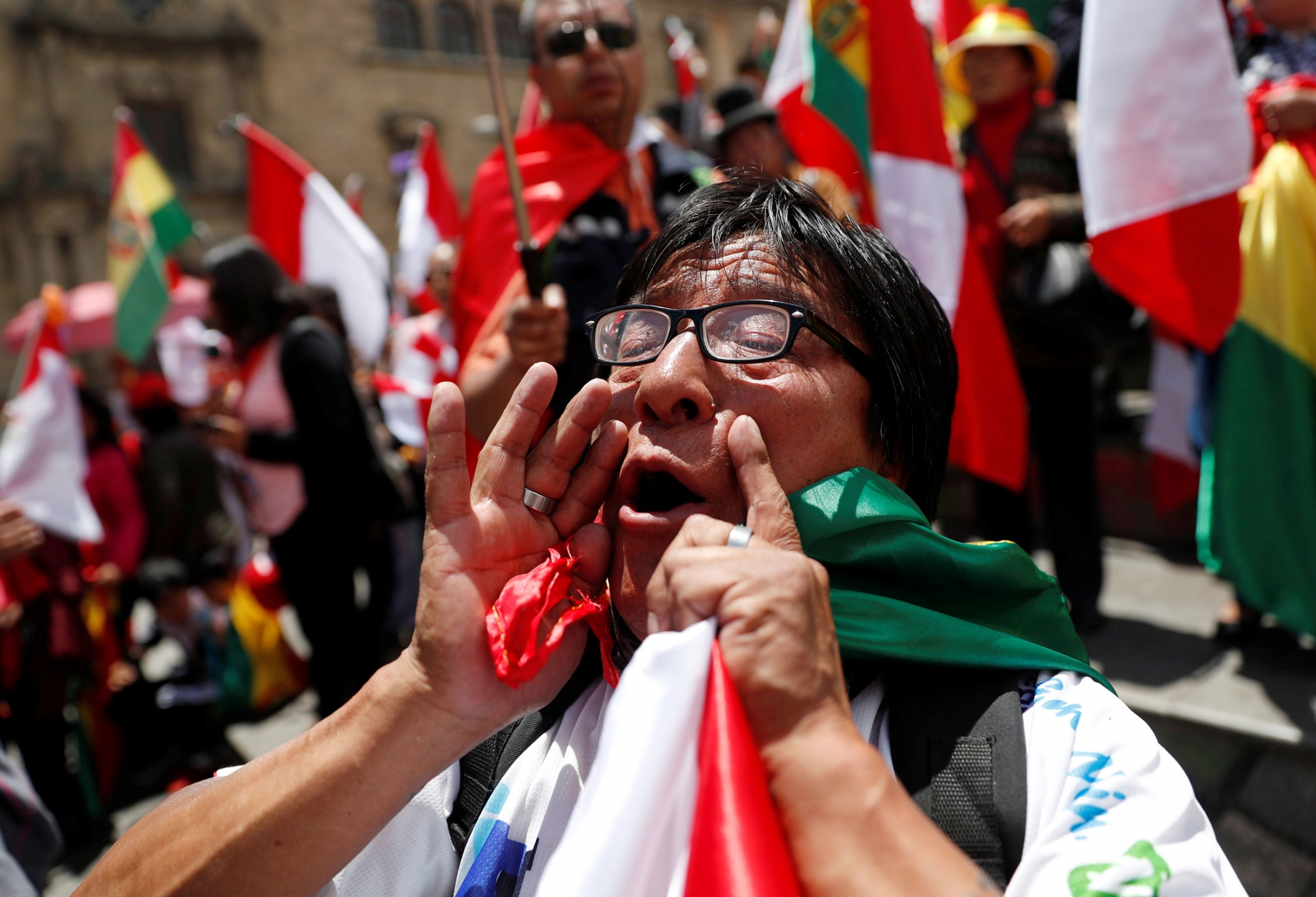 A demonstrator is shown with their hands around their mouth shouting and holding a Bolivian flag.
