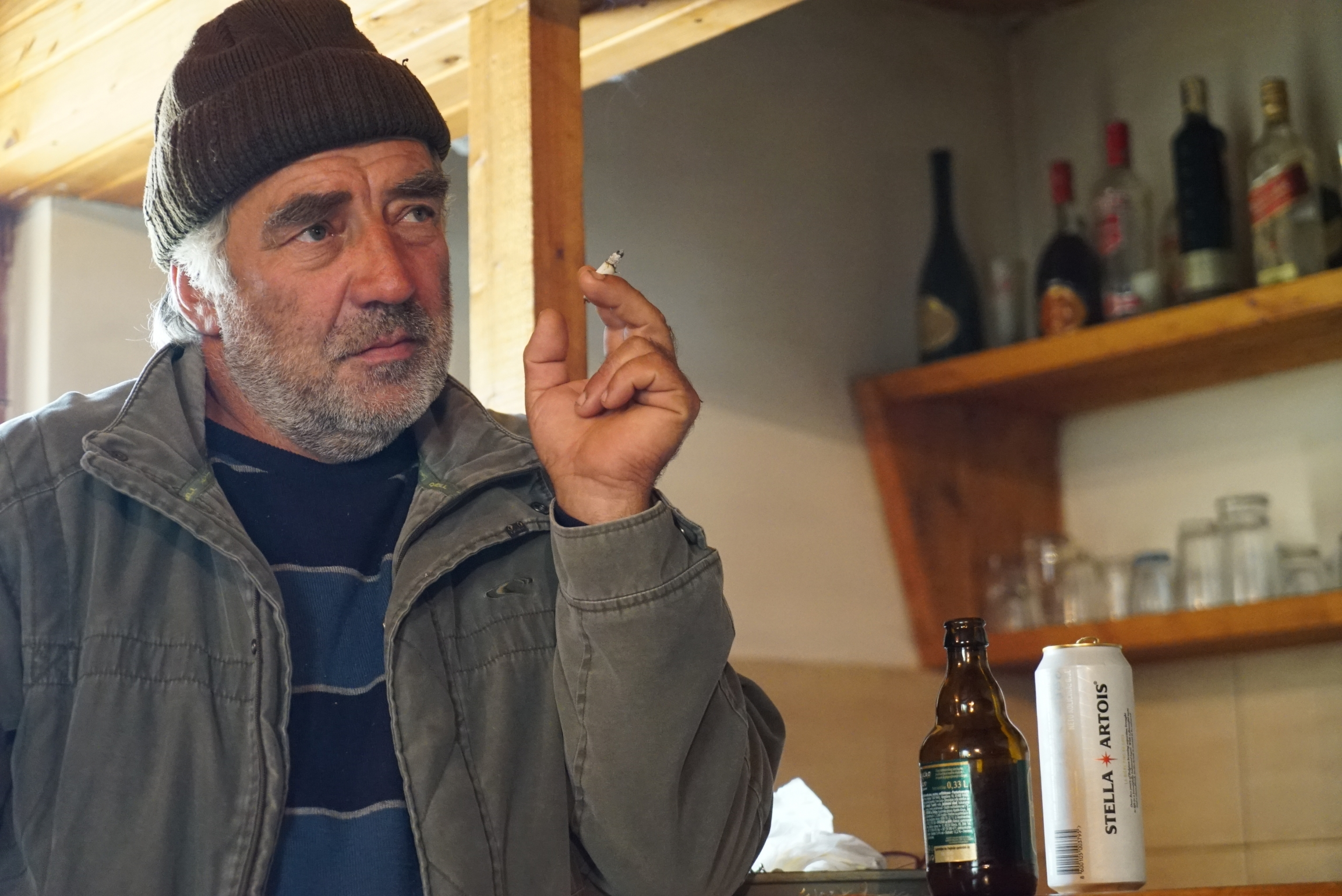 A man wearing a hat smokes a cigarette at the bar with an open beer