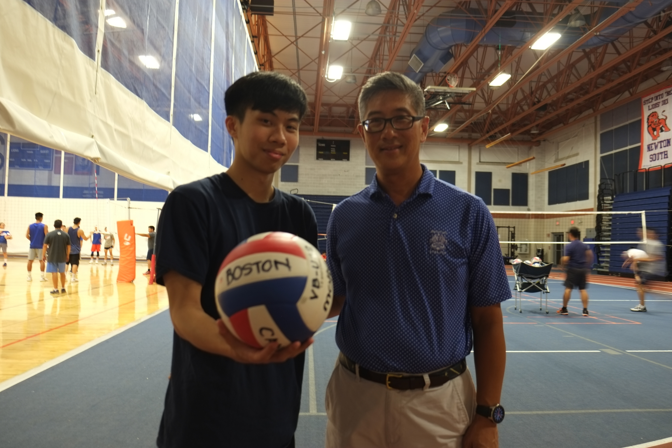 A young Asian man and older Asian man stand next to each other with a volleyball