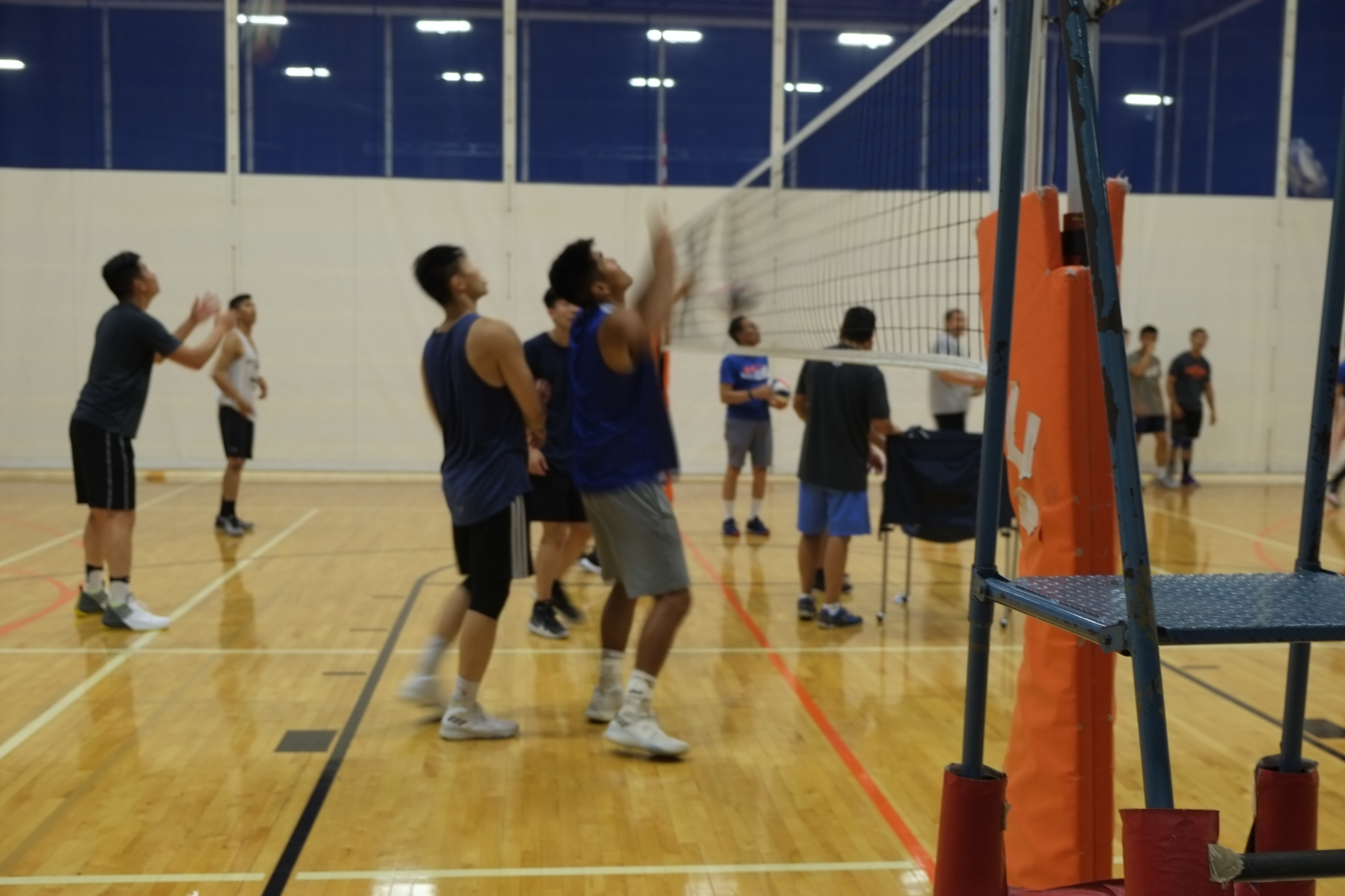 Asian men play a volleyball game in uniforms on a court