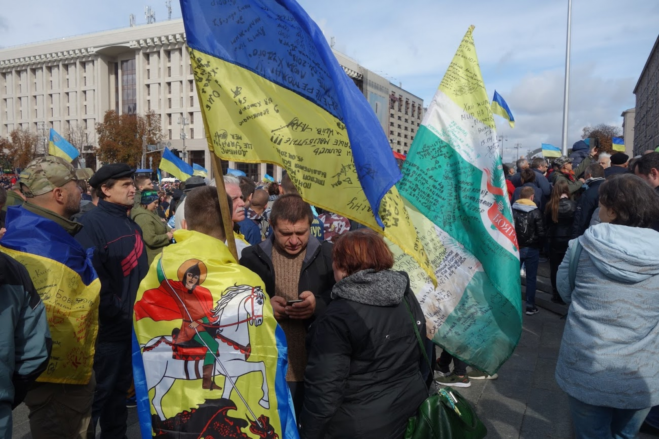 Protesters holding Ukrainian flags gather on Kyiv's Independence Square.