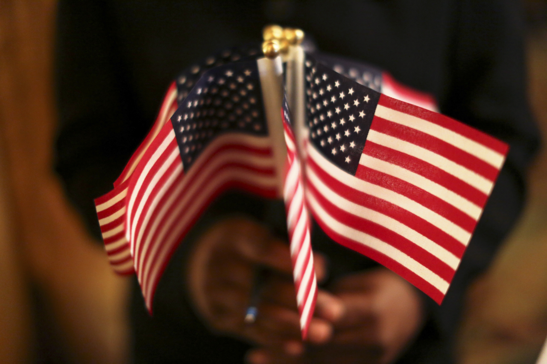 A woman holds a cluster of US flags during a US Citizenship and Immigration Services naturalization ceremony in Oakland, California, on Aug. 13, 2013.