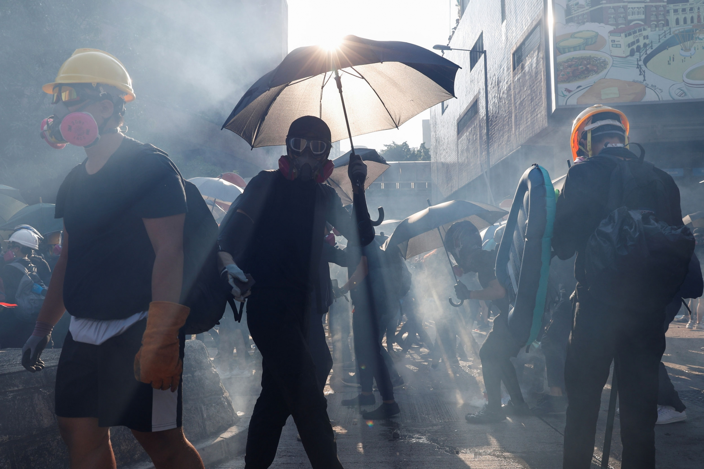 Several protesters are shown wearing gas masks and one holding an umbrella with the sun glaring above it.