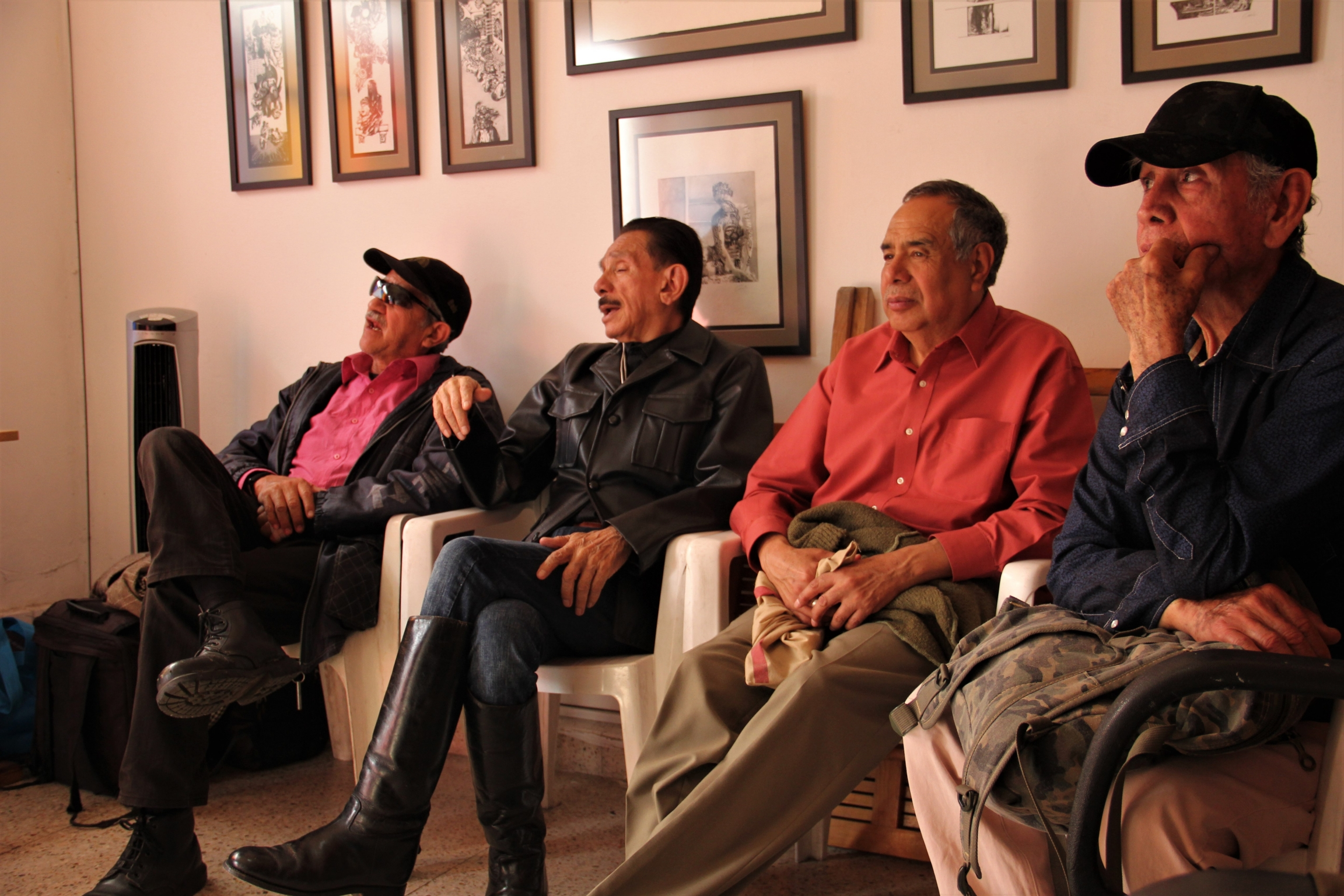 Four men sit on chairs in a small room