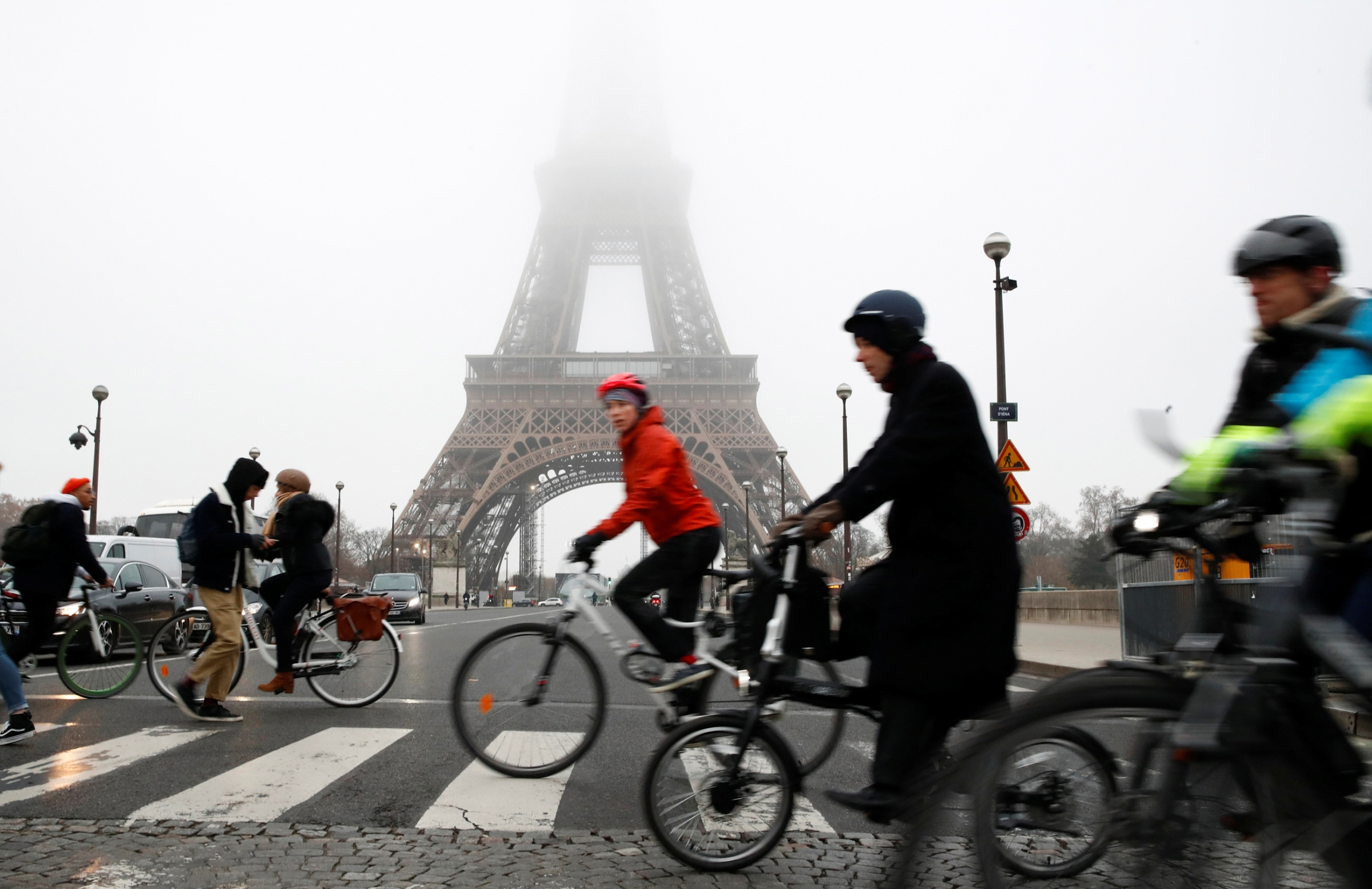 Several people are shown riding bicycles and crossing the street near the Eiffel Tower during a strike by all unions of the Paris transport network.