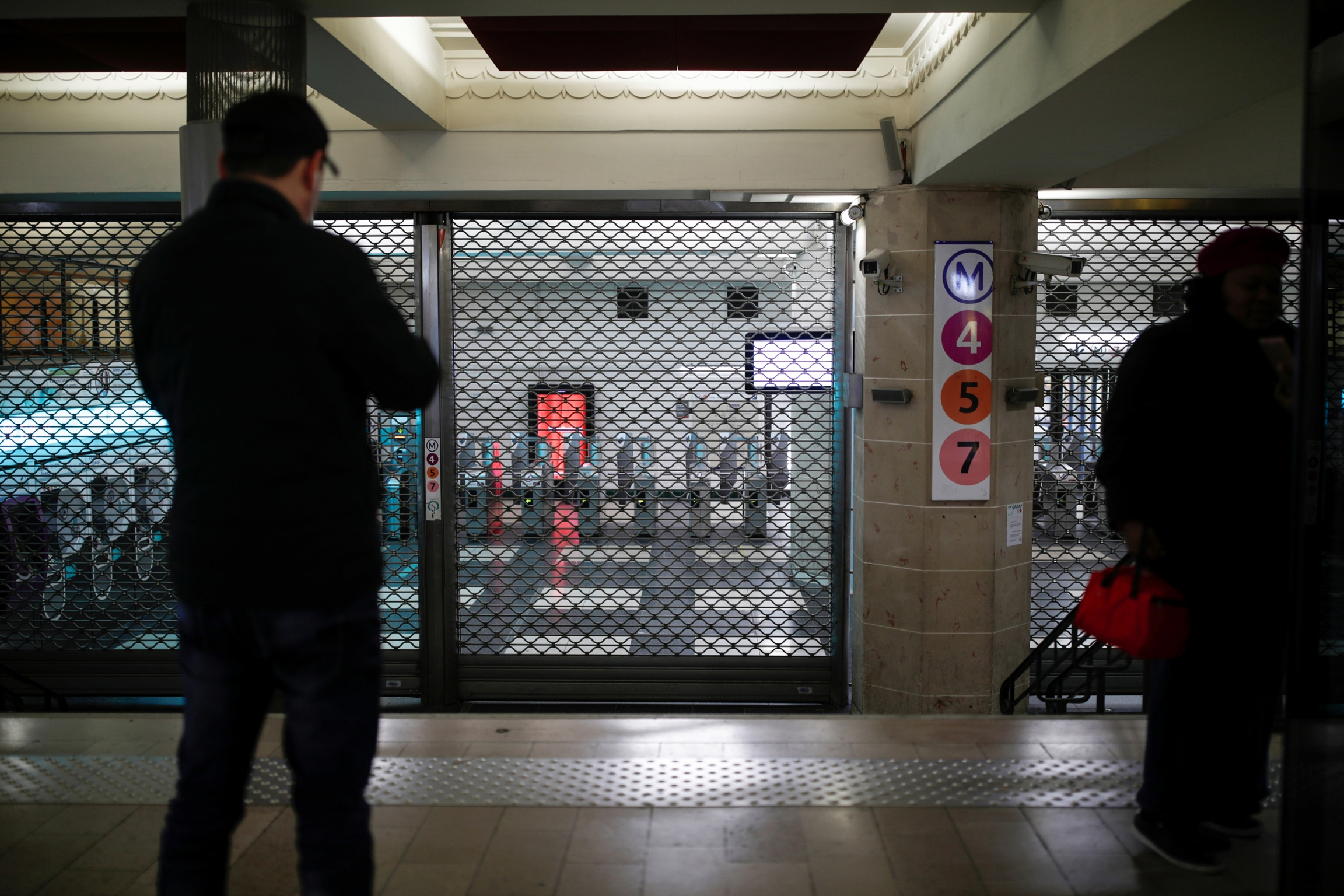 Metal gates block a closed entrance at the Gare de l'Est metro station with a man standing in shadow in the nearground looking on.