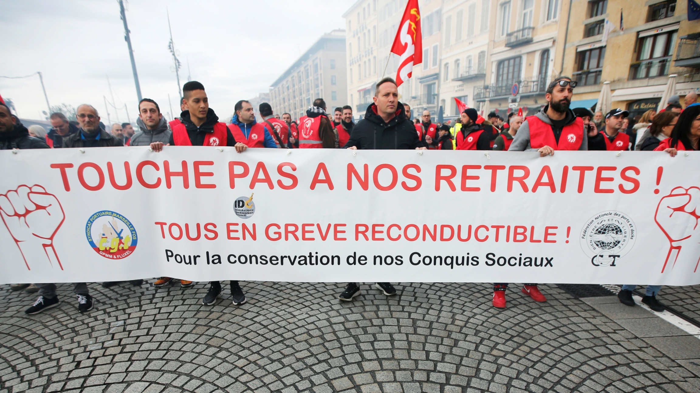 """A large group of protesters are shown in the street holding a banner during a demonstration in Marseille. The banner reads, """"Don't touch my pension."""""""