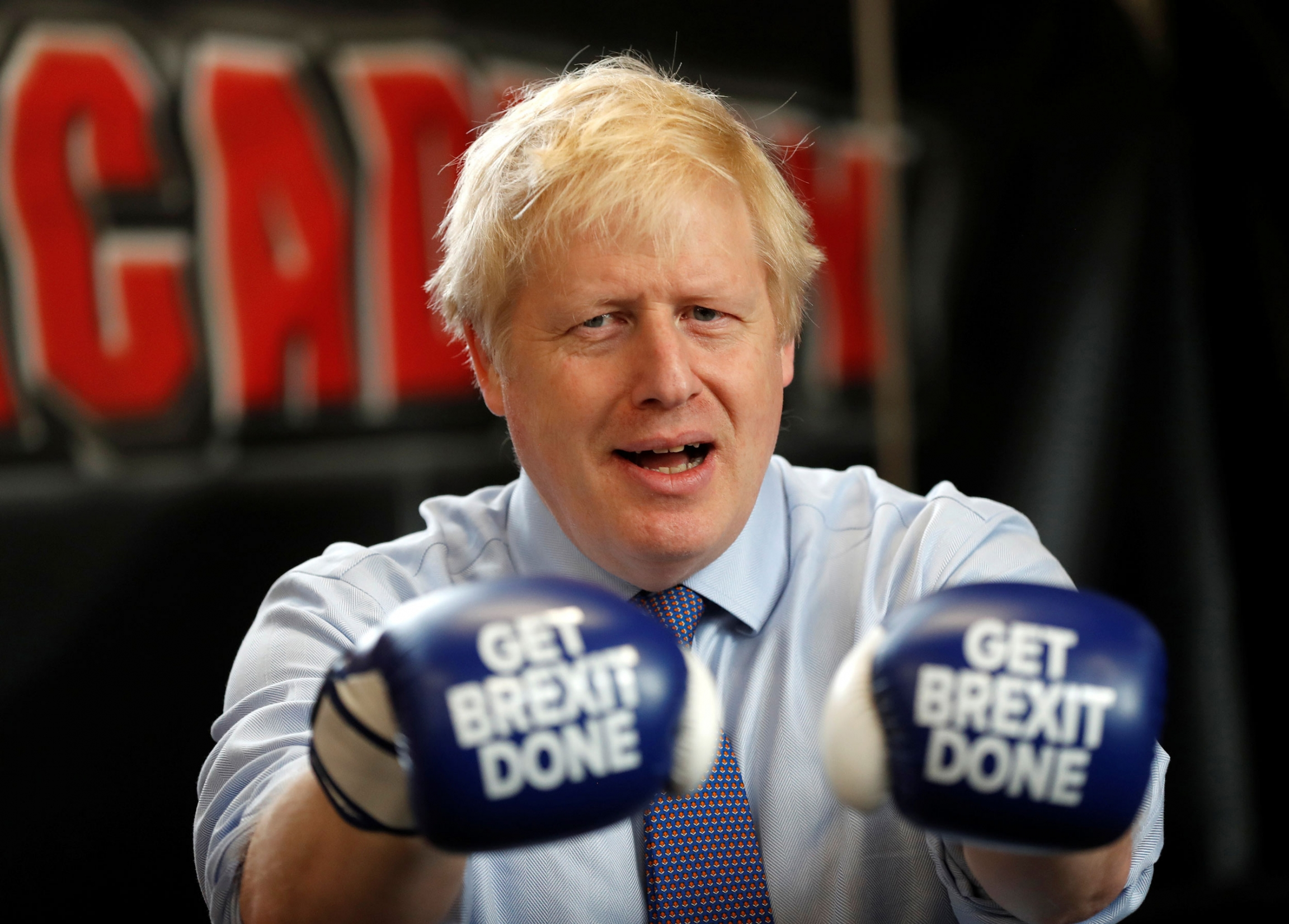 "Britain's Prime Minister Boris Johnson is shown wearing blue boxing gloves with the words ""Get Brexit Done"" printed on them."