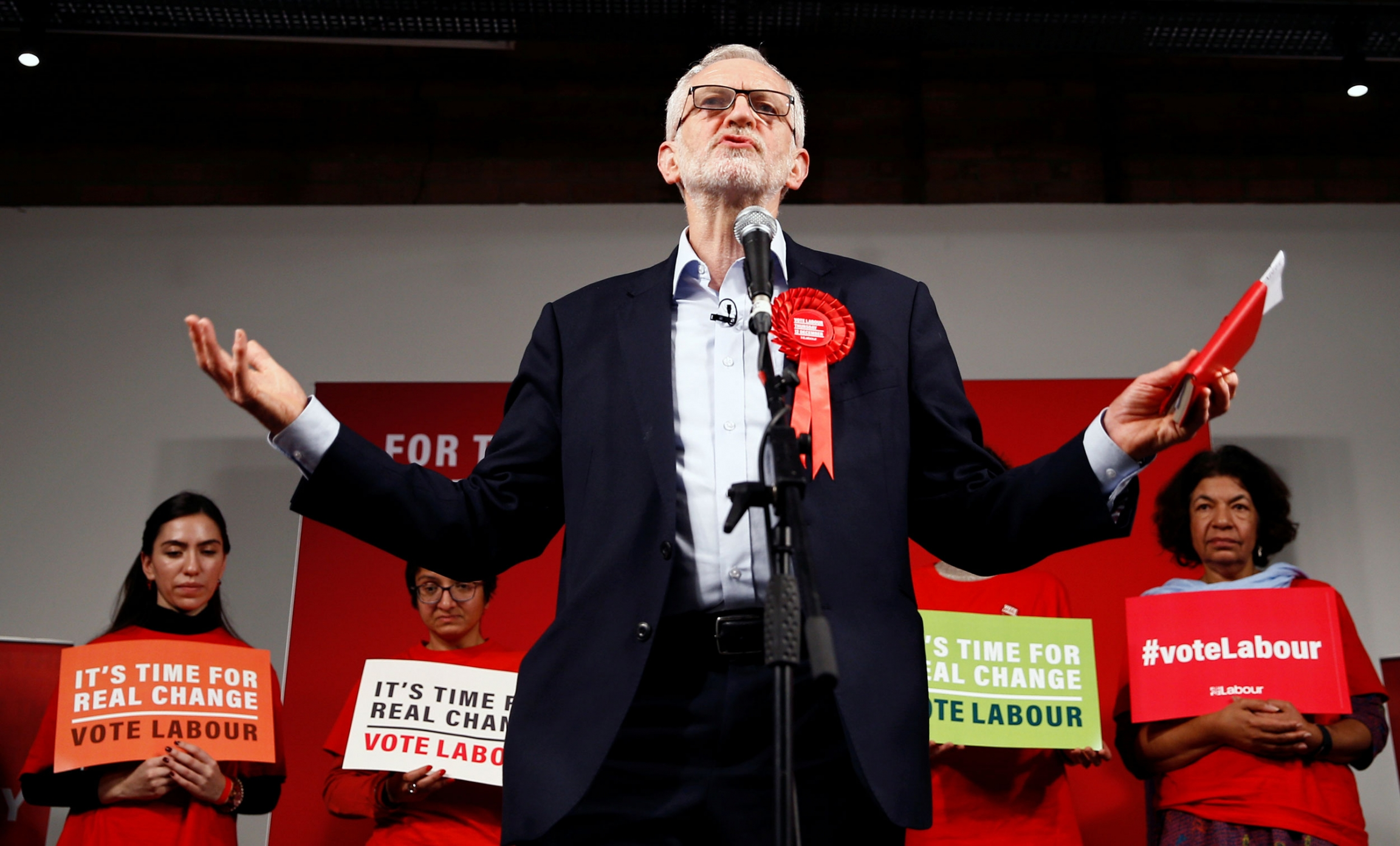 Britain's opposition Labour Party leader Jeremy Corbyn is shown standing a microphone wearing a large red ribbon and holding a red book.