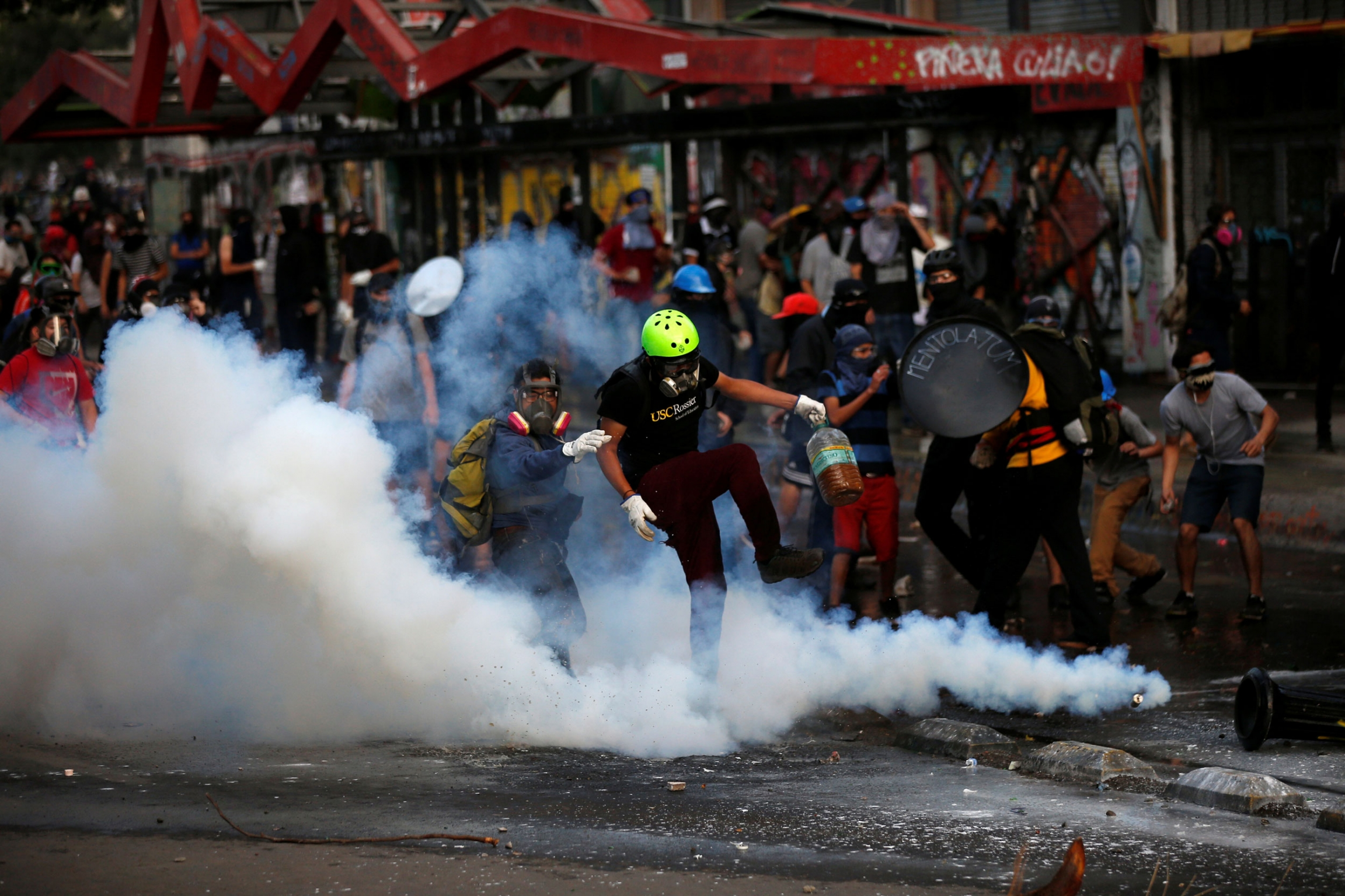 A goupr of demonstrators wearing gas masks are show surrounded by clouds of tear gas.