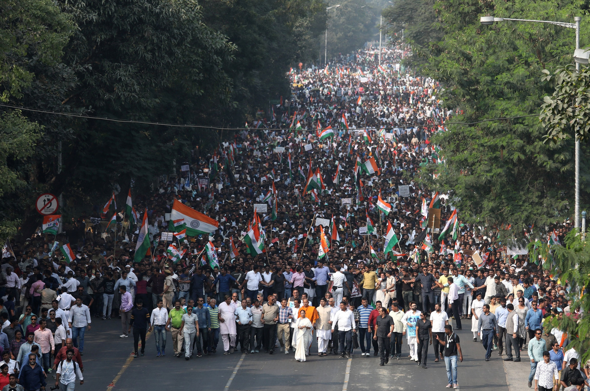 A street is filled with hundreds of protesters, many carrying India's national flag.