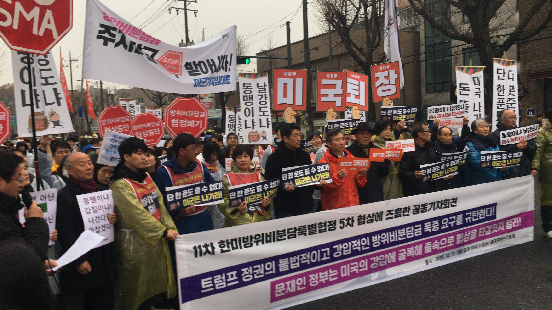 A group of protesters march with a large banner with large words in Korean language