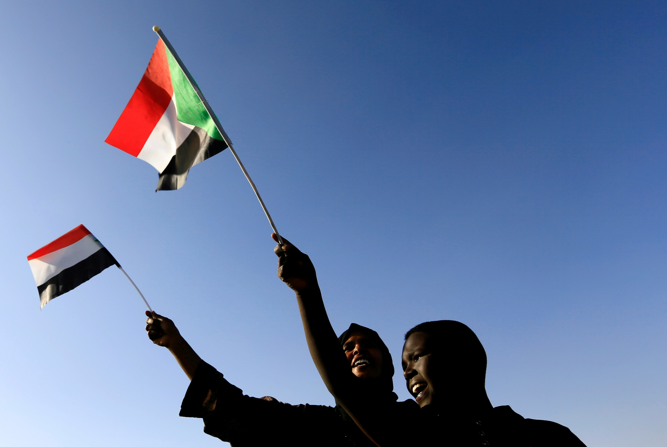 Two Sudanese people wave their flag against blue backdrop