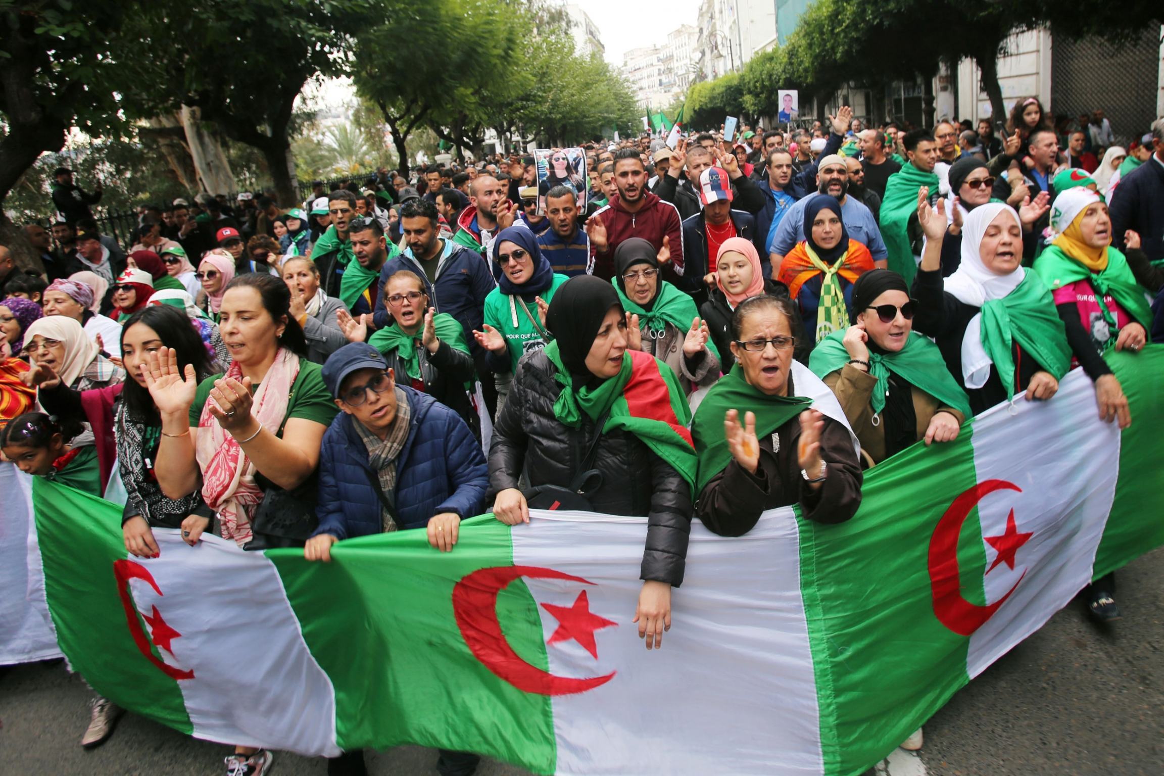 A large group of demonstrators are shown filling a street in Algiers with the Algerian flag in front of them.