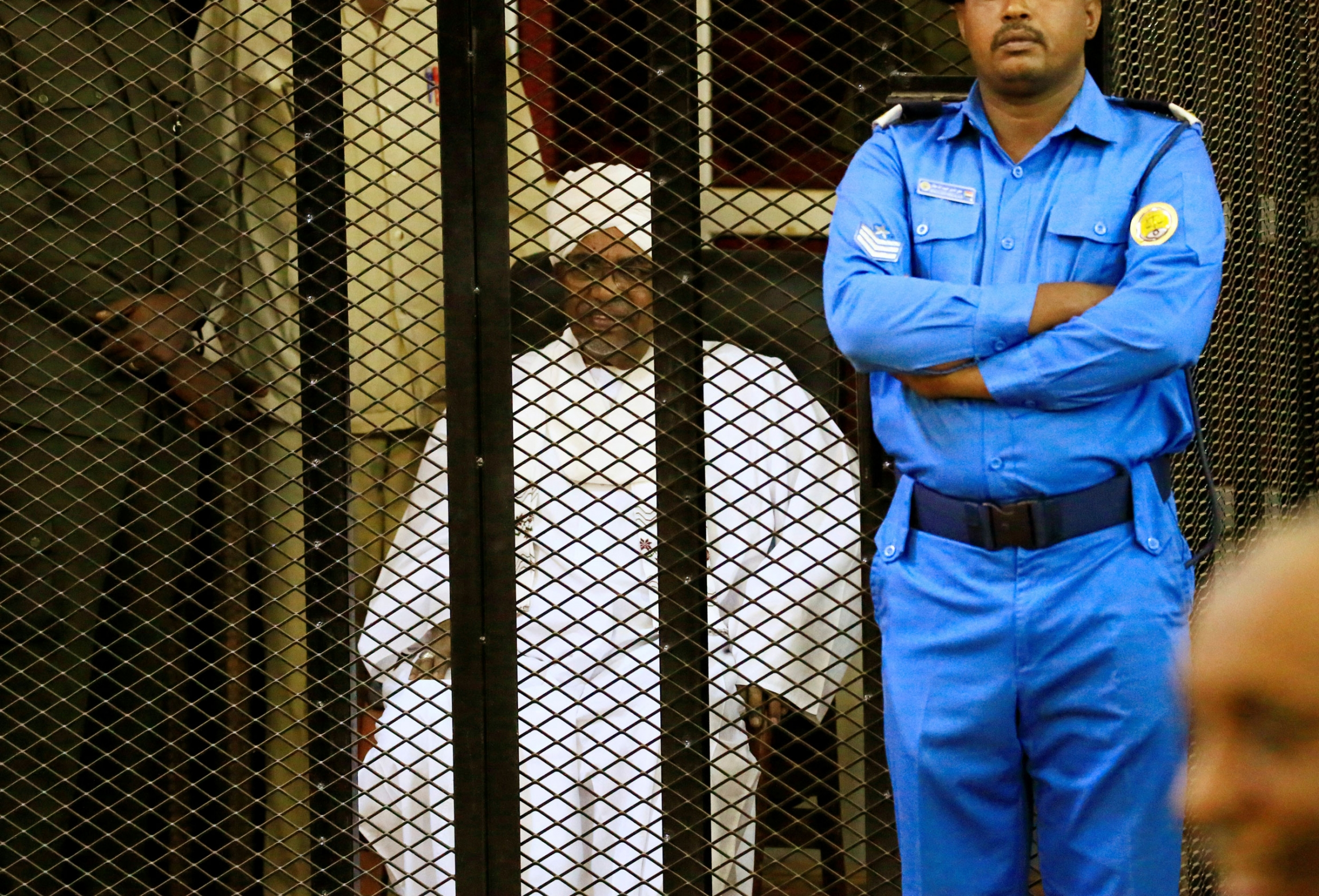 Sudanese former president Omar al-Bashir is shown sitting in all white and inside a metal cage with a guard standing beside it.