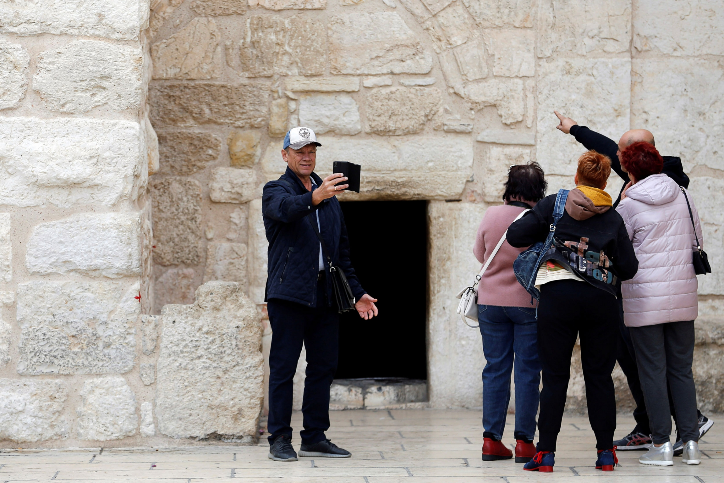 A tourist wearing a ball cap is shown with four other tourists taking a selfie outside the Church of the Nativity.